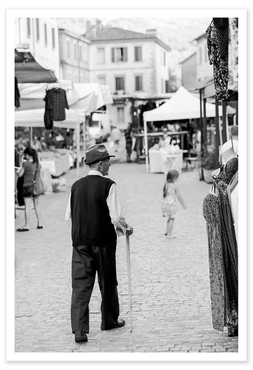 An old man strolls through  centro  in Castel Del Rio, Italy.  Exif Data: 1/160 sec ; f/4.5 ; ISO 200