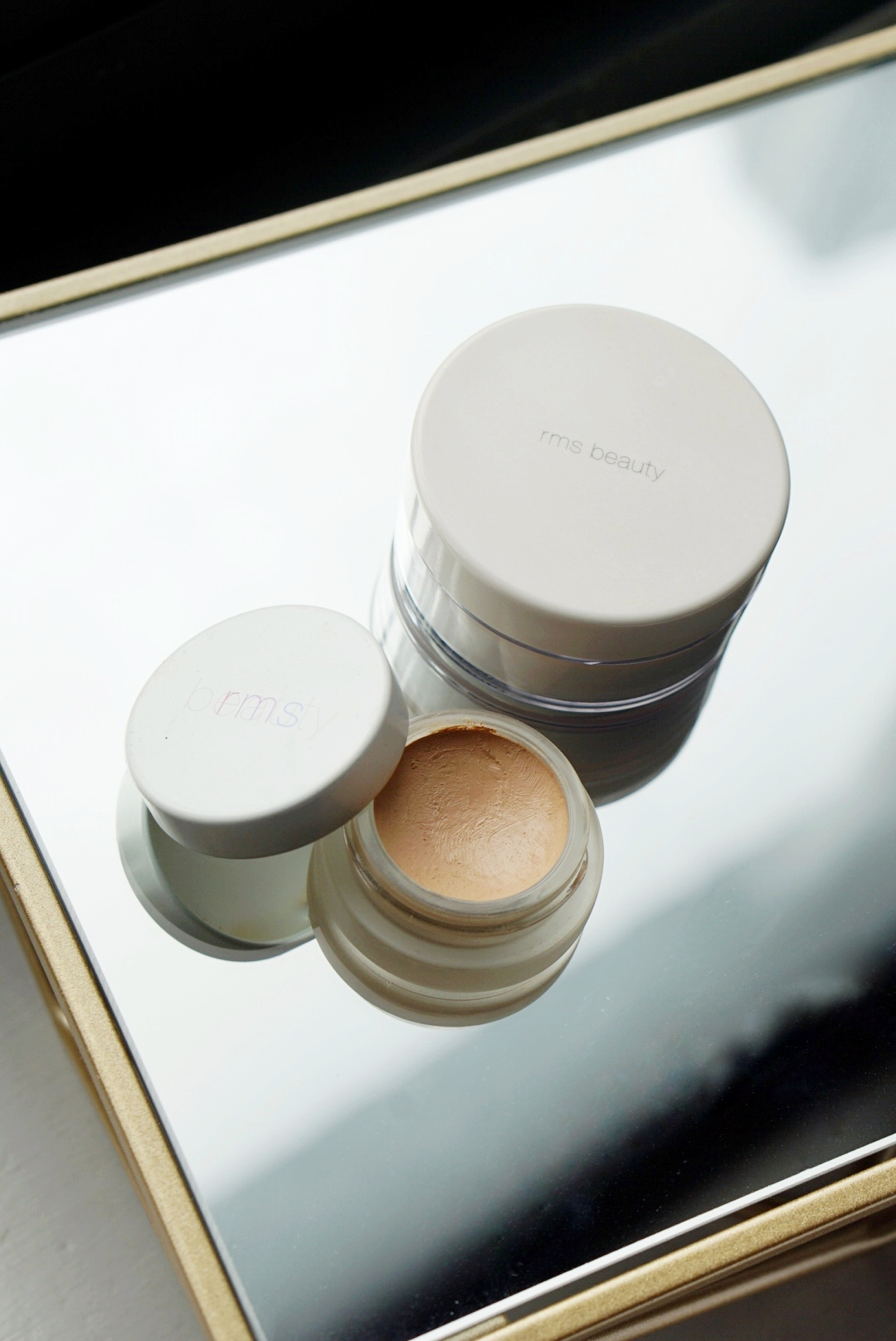 """Un Cover Up by RMS Beauty - RMS Beauty's Un Cover Up works as a foundation as well as a concealer. The product is crafted from raw, organic ingredients and has a moisturizing formula. The color I have is No. 22.What I love: This foundation is one of my favorites out of the 5. It gives me that bouncy, dewy look! It doesn't dry my skin and helps reduce redness on my sensitive cheeks. The container is small and light, so it is very easy to travel with. And I mean even on a daily basis; it's great to have in my bag in case I need touchups before a photo shoot or an event.What I'd like to change: Initially I thought it'd be great if the foundation had SPF for sun protection! But I later learned from Laura Saur, Director of Social Media at RMS Beauty, that """"… you will not find any of our (RMS Beauty) products to include unnatural SPF ingredients/additives as that is what diminishes it from being a natural and clean beauty product. Most makeup products that have SPF included contain synthetic ingredients, which are not clean."""""""