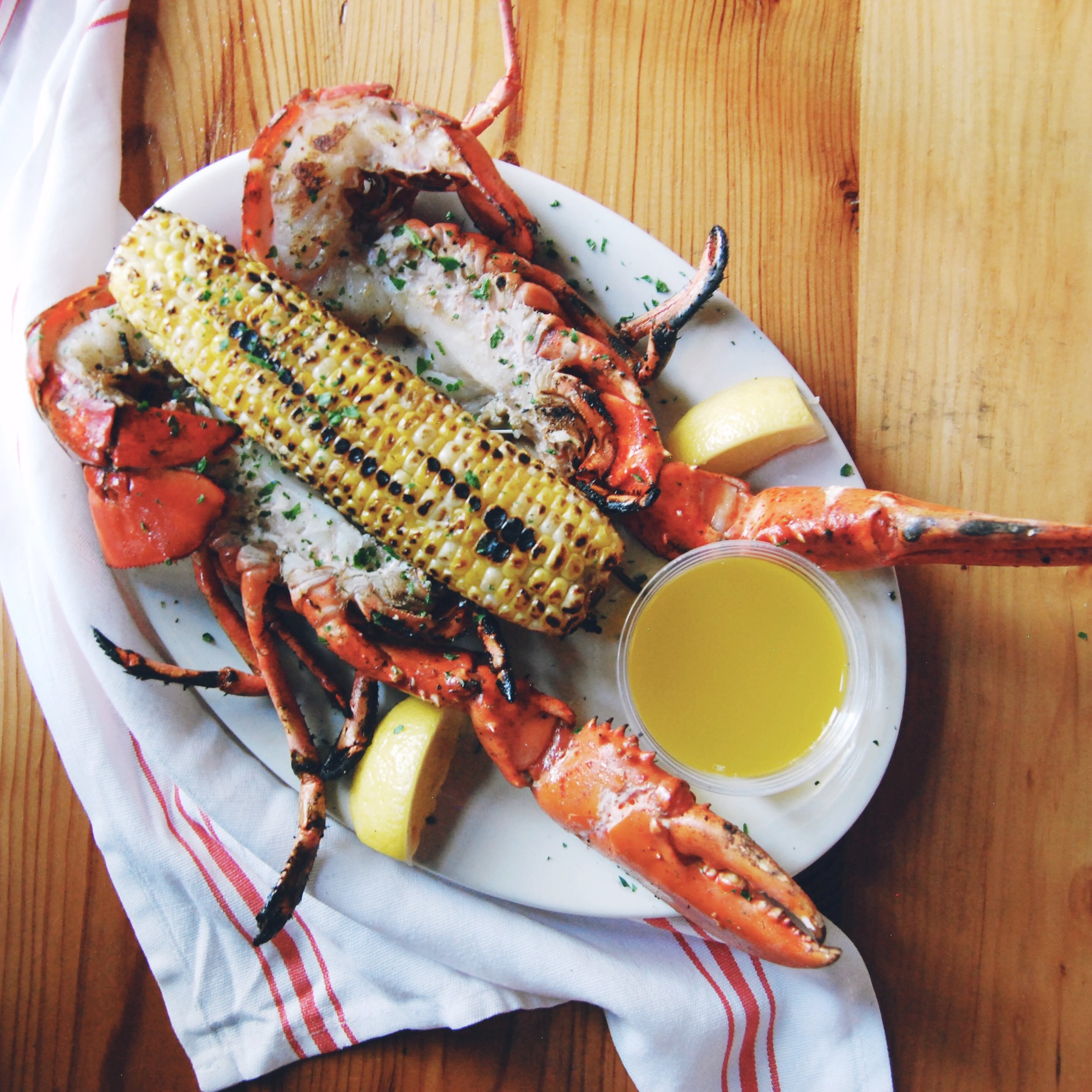 GRILLED LOBSTER & CORN   At most New England seafood restaurants you'll find boiled lobster. Here, we butterfly and grill ours, enhancing its natural flavor. Not only is it delicious, but by opening up the lobster, we've done most of the work for you that usually comes with ordering lobster!