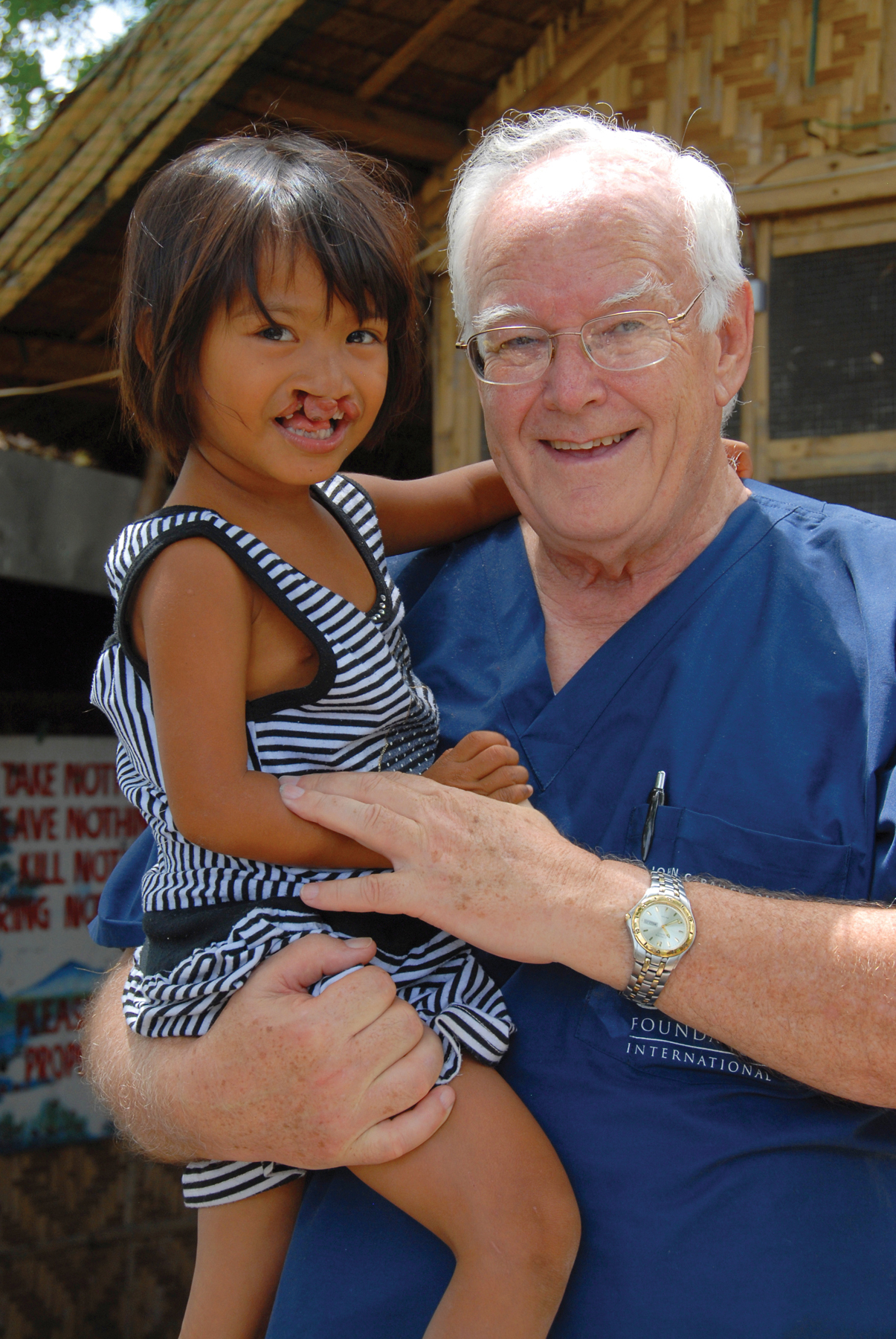 Dr. John Bailey  holds a dear child with a severe cleft lip on the island of Cebu in the Philippines.