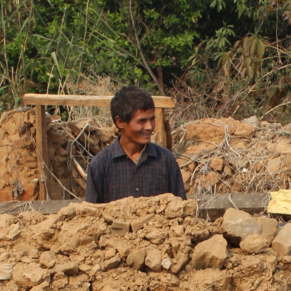 Ramsharan Napit, 45, hearing impaired, amid the rubble of his house.