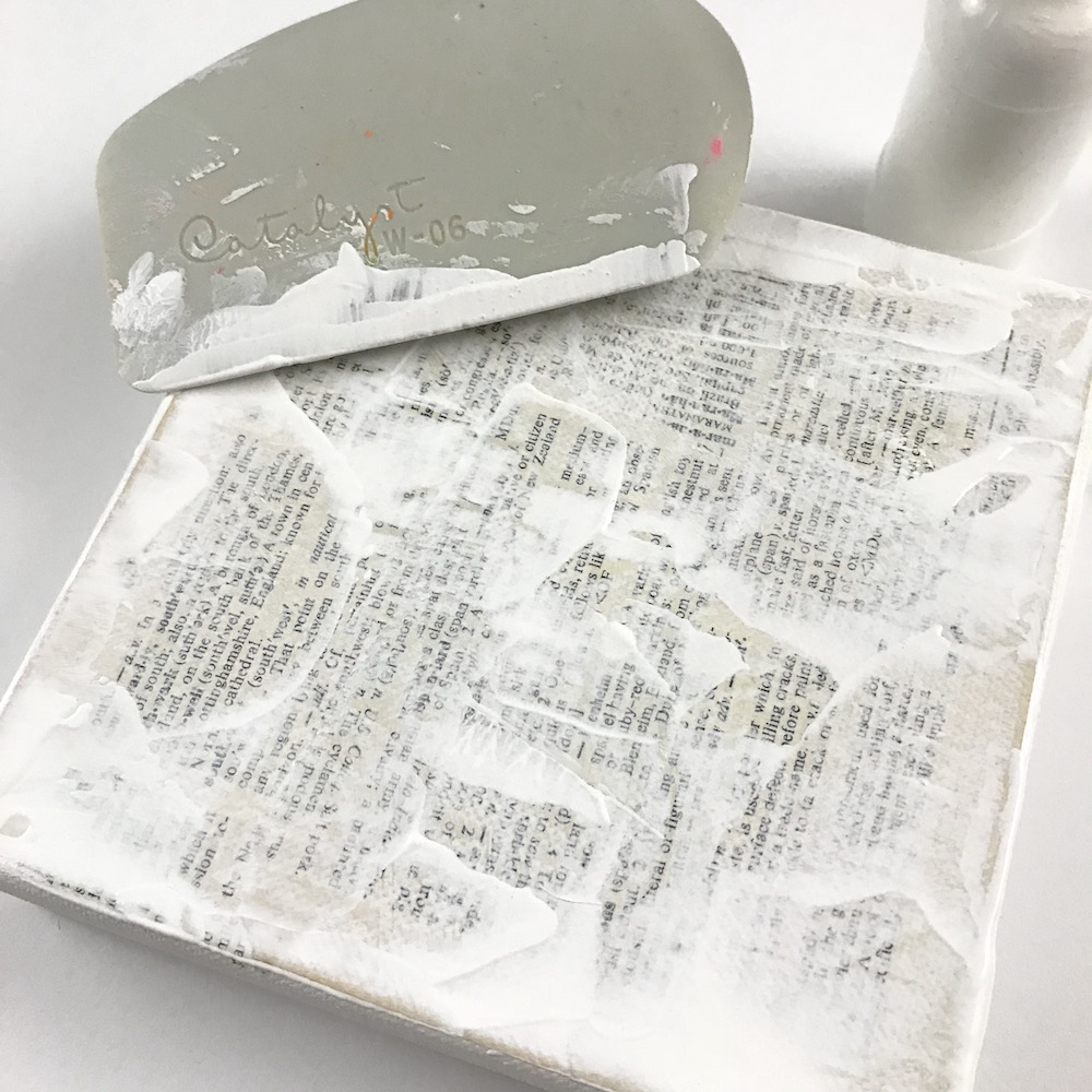Step 2: - Apply gesso on top of the paper. Scrape the gesso so it's thin enough to see through in some places. Let dry.