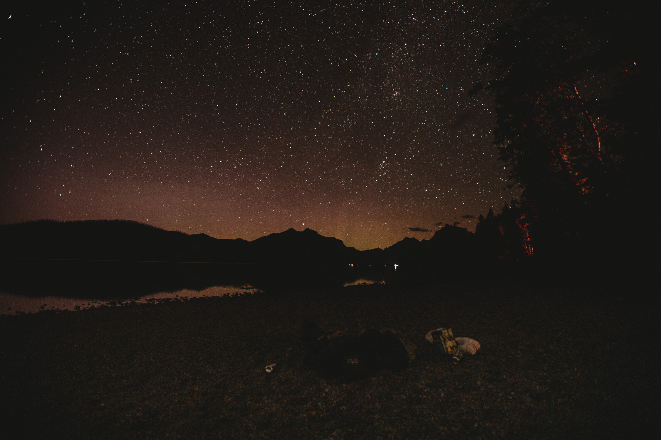 Ali and Tyler-Moss laying together under the stars at the end of their elopement day.