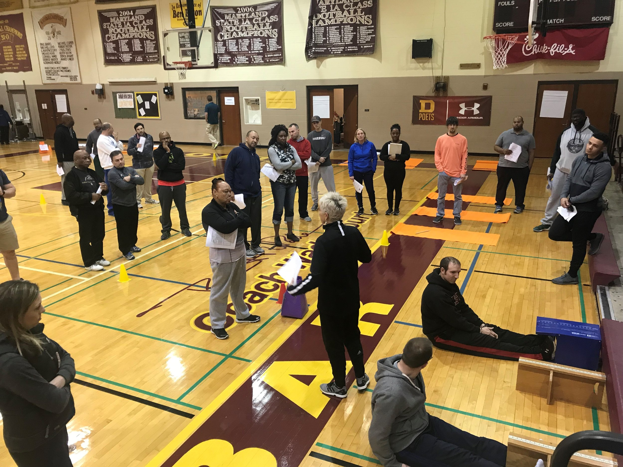 At one of the training stations, PE teachers gathered around to role-play an activity. Photo by Project Play: Baltimore.