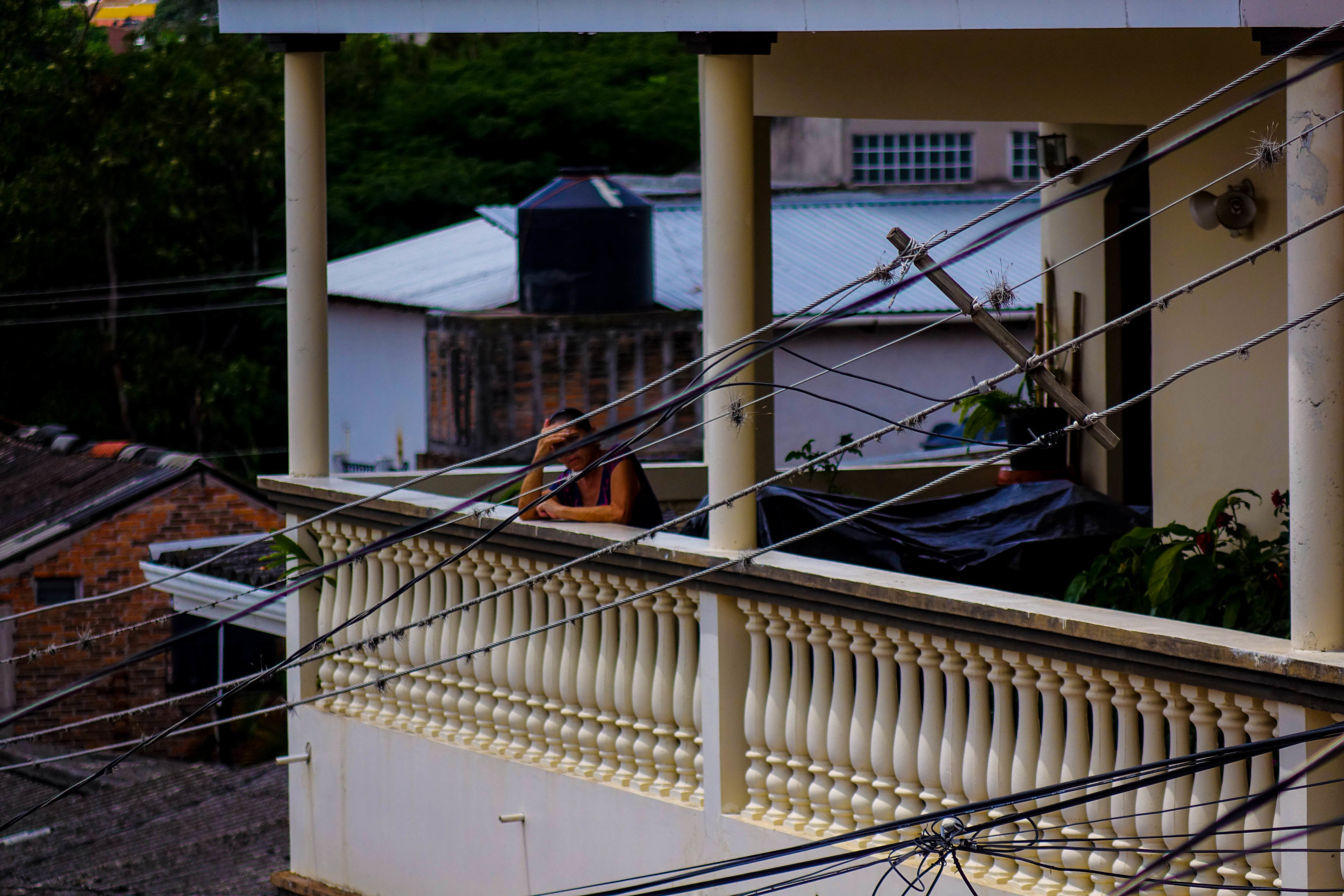 A woman standing on the balcony of her home in Tegucigalpa.