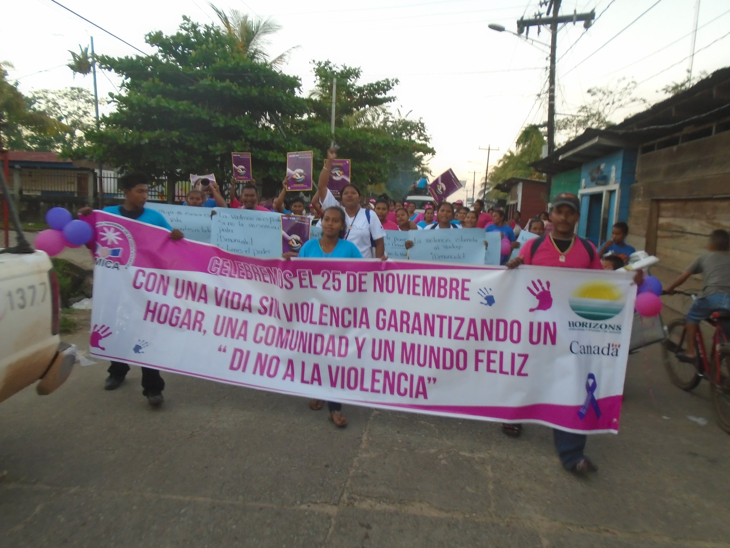 """Members from Horizons' partner organization AMICA participate in an anti-violence march holding a banner that says: """"Life without violence guarantees a happy home, community and world - Say no to violence""""."""