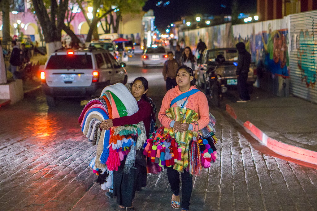 Street vendors selling blankets and knitted items at night in San Cristobal de las Casas, Chiapas, Mexico. Women often sell items in the street, while men work low-income agricultural jobs in Chiapas.