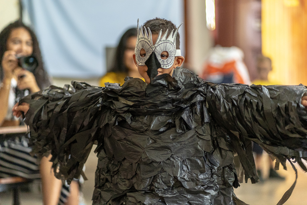 A young boy showing off his bird costume he made using 100% recycled materials at the Madres Maestra community centre.