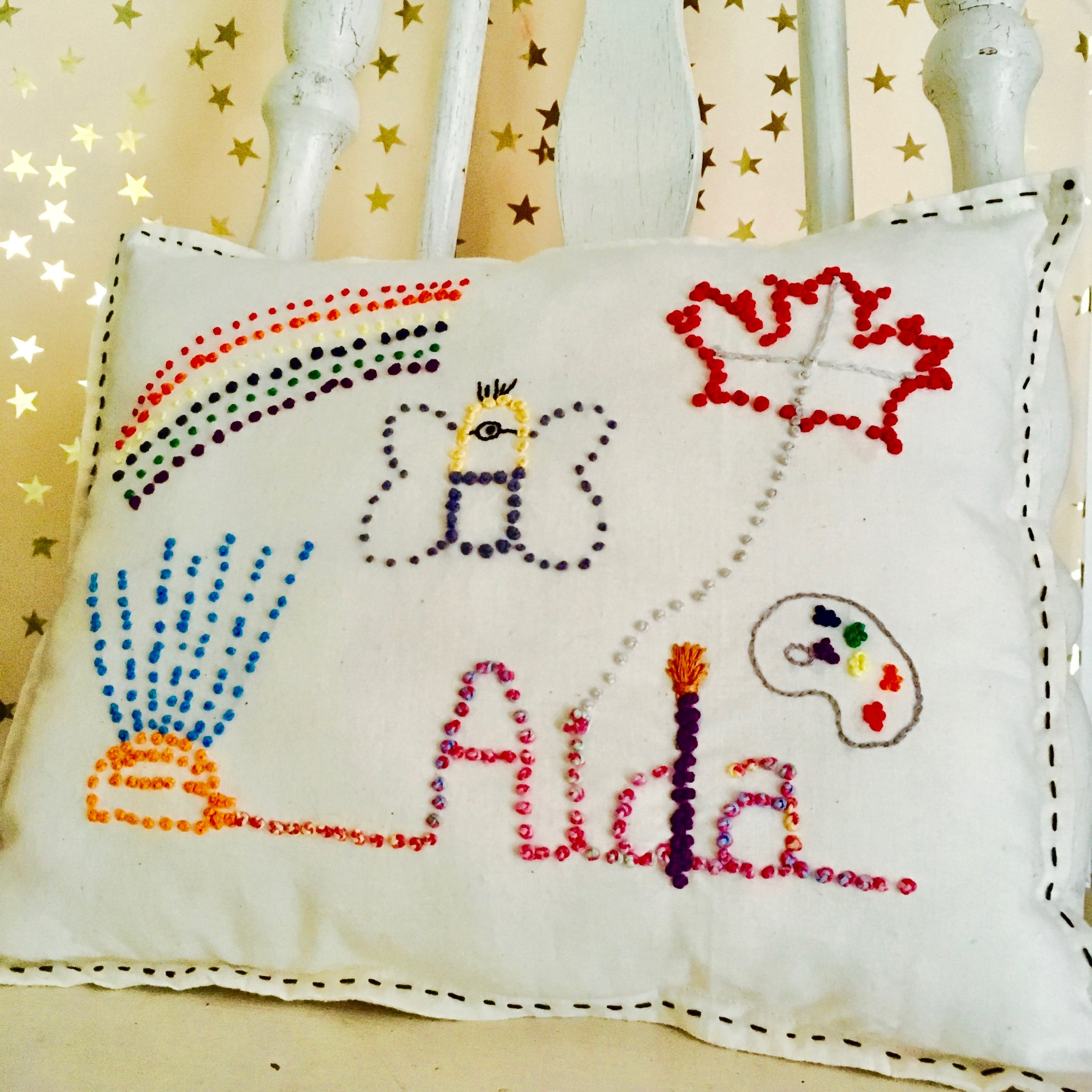 Image Description: White pillow with black sewing around the edges sitting on white chair with a pink and gold star background. The pillow has various images such as a sprinkler, rainbow, butterfly, Canadian maple leaf, a paint palette, and the name Aida.