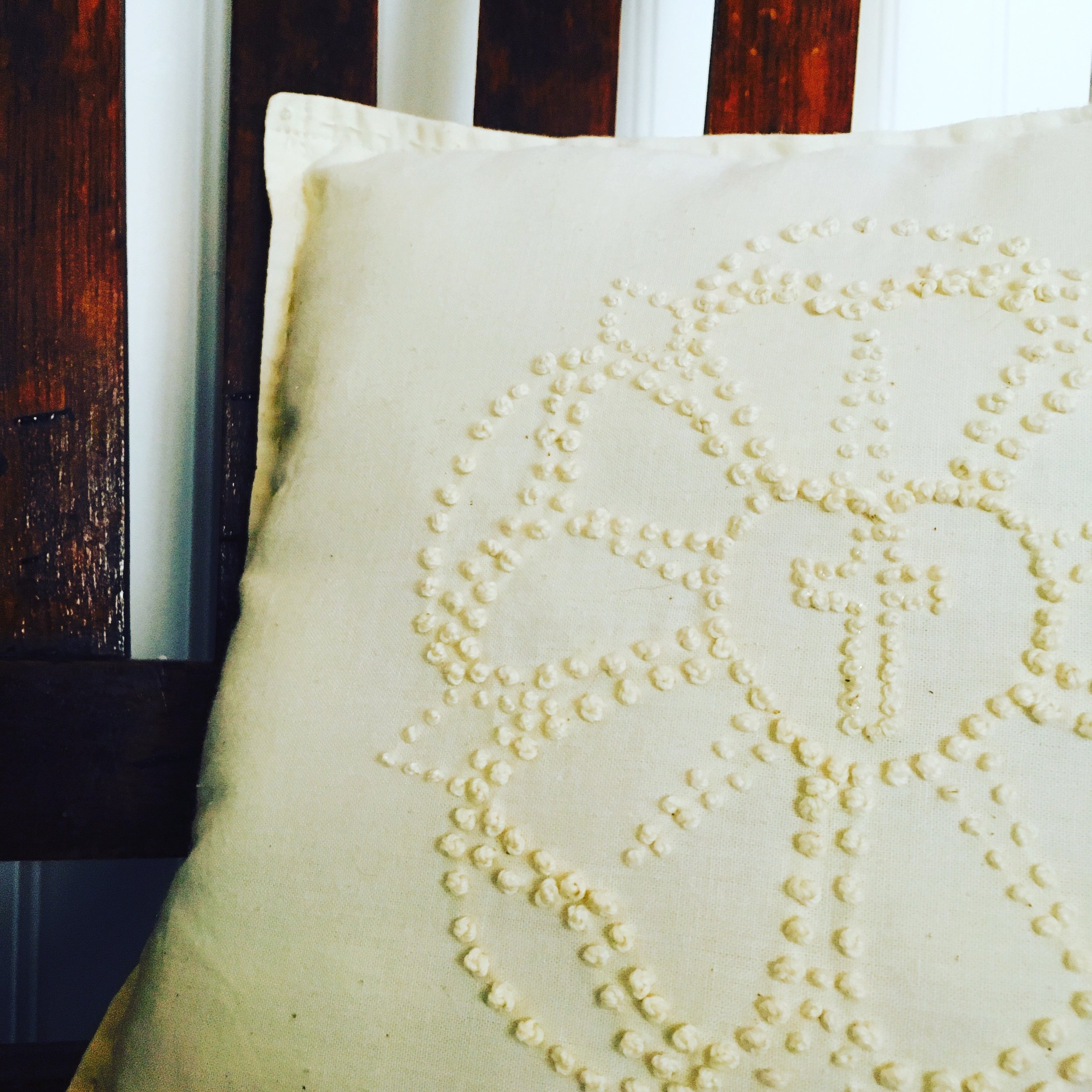 Image Description: White pillow with the Lutheran Rose in candle-wicking on the front. Sitting on a brown chair with a white bead board background.