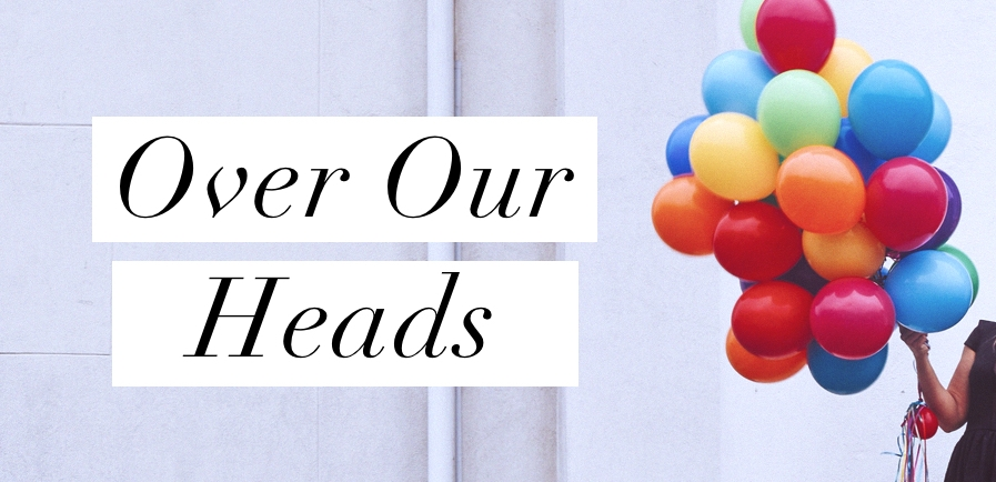 Image Description: Individual holding a bunch of different colored balloons to the right side. The words 'Over Our Heads' in black on white stripes to the left side of the image.