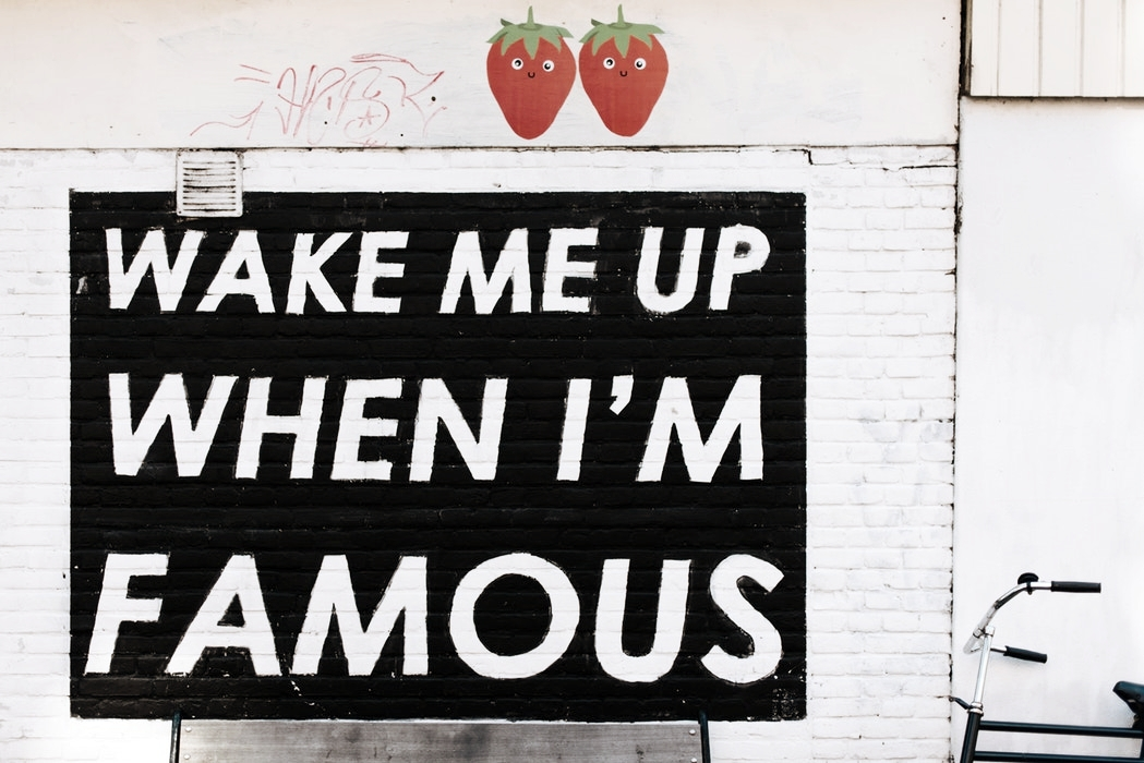 """Image description: Black square painted on a wall with the words """"Wake me up when I'm famous"""" in big white letters."""