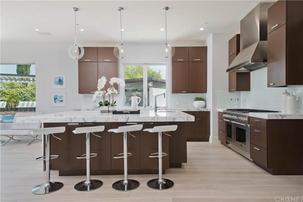 The designer kitchen features Calcutta Gold Marble, top-of-the-line Thermador appliances, and custom African finished cabinetry.