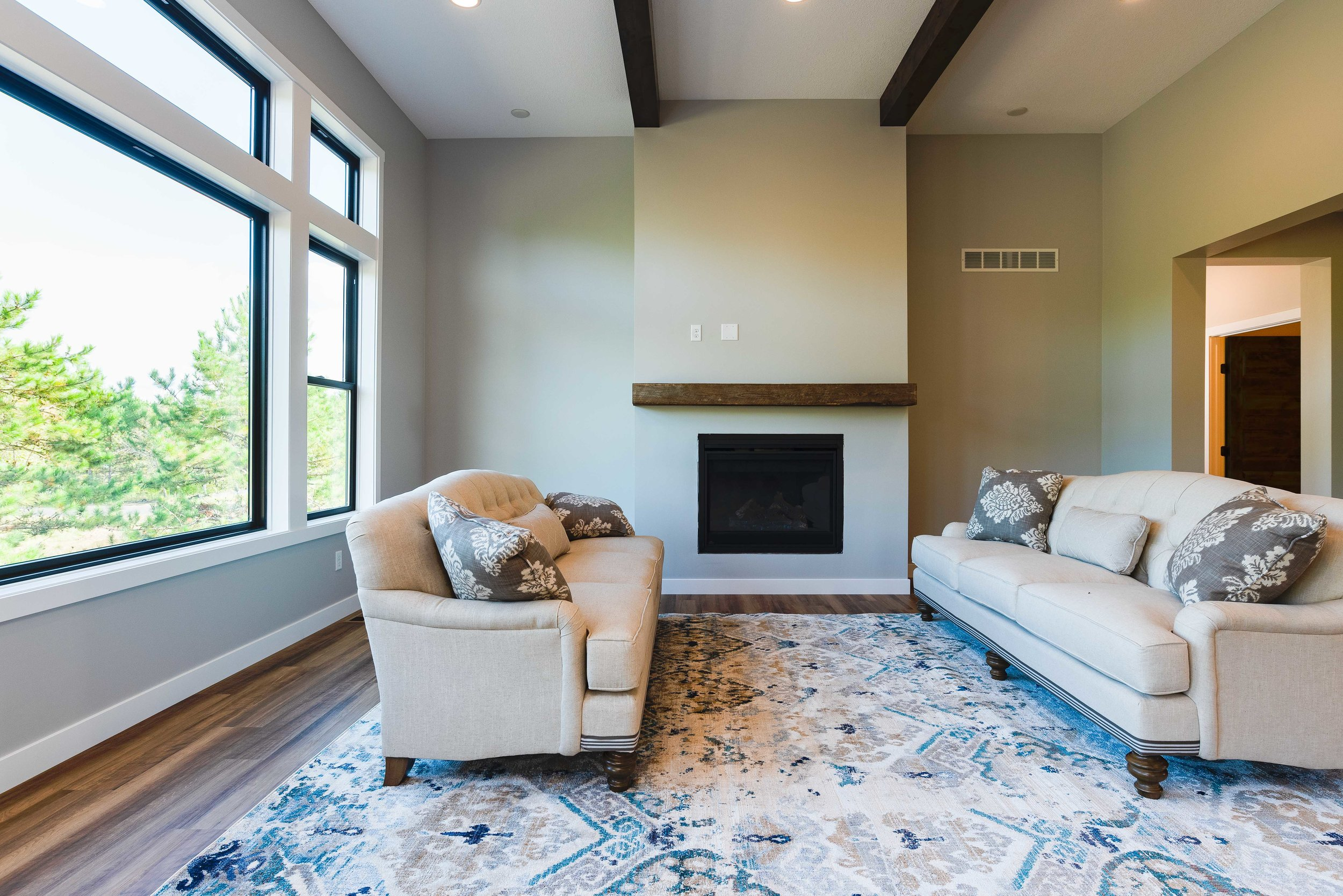 This living room features a simple, yet beautiful mantle over the fireplace as well as big windows to let in plenty of light!
