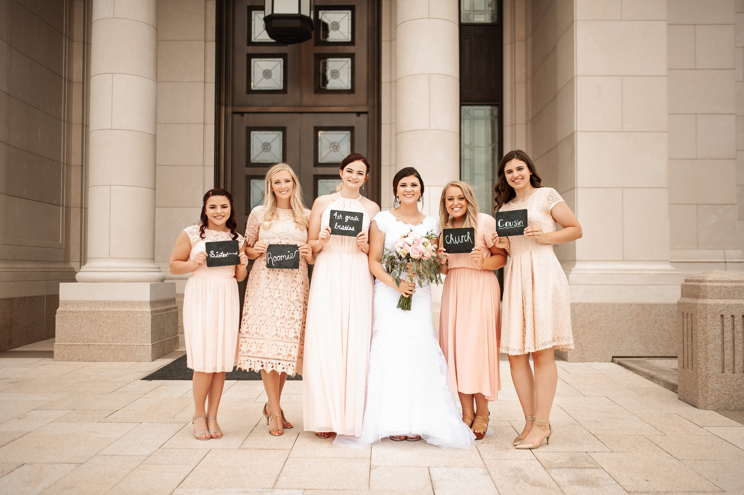 Bridal party with cute signs showing how they met the bride, Allie.