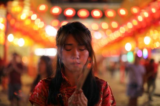 A woman lights incense while praying in a Chinese temple during the celebration of the Lunar New Year in Chinatown in Bangkok, Thailand. Picture: Jorge Silva/Reuters