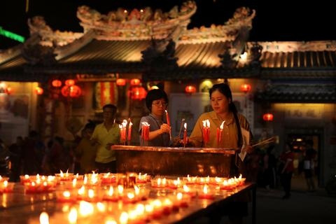 Women light candles while praying in a Chinese temple during the celebration of the Lunar New Year in Chinatown in Bangkok, Thailand. Picture: Jorge Silva/Reuters