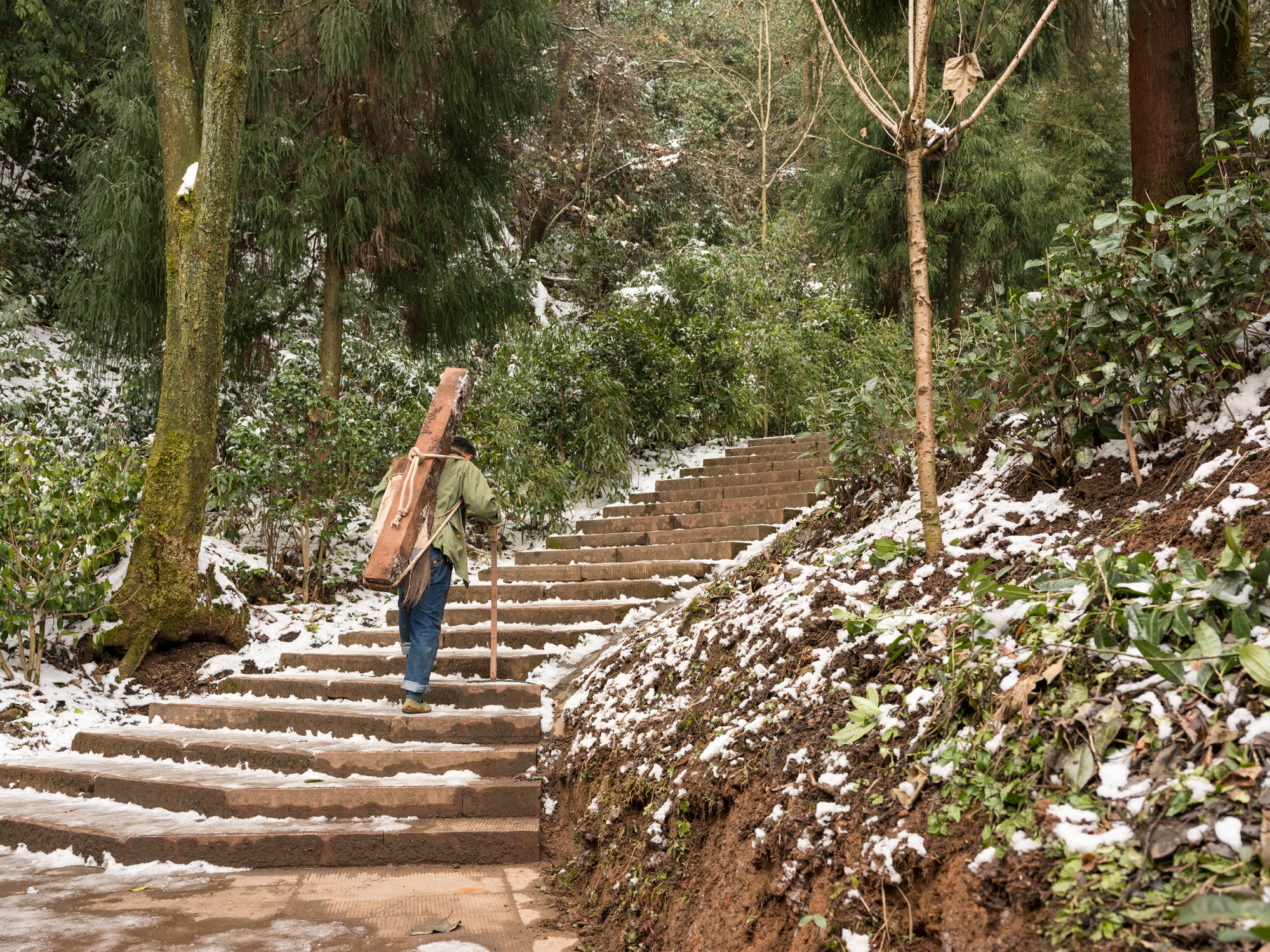 A worker carries a wooden beam up the ice-covered steps of Mengding mountain.