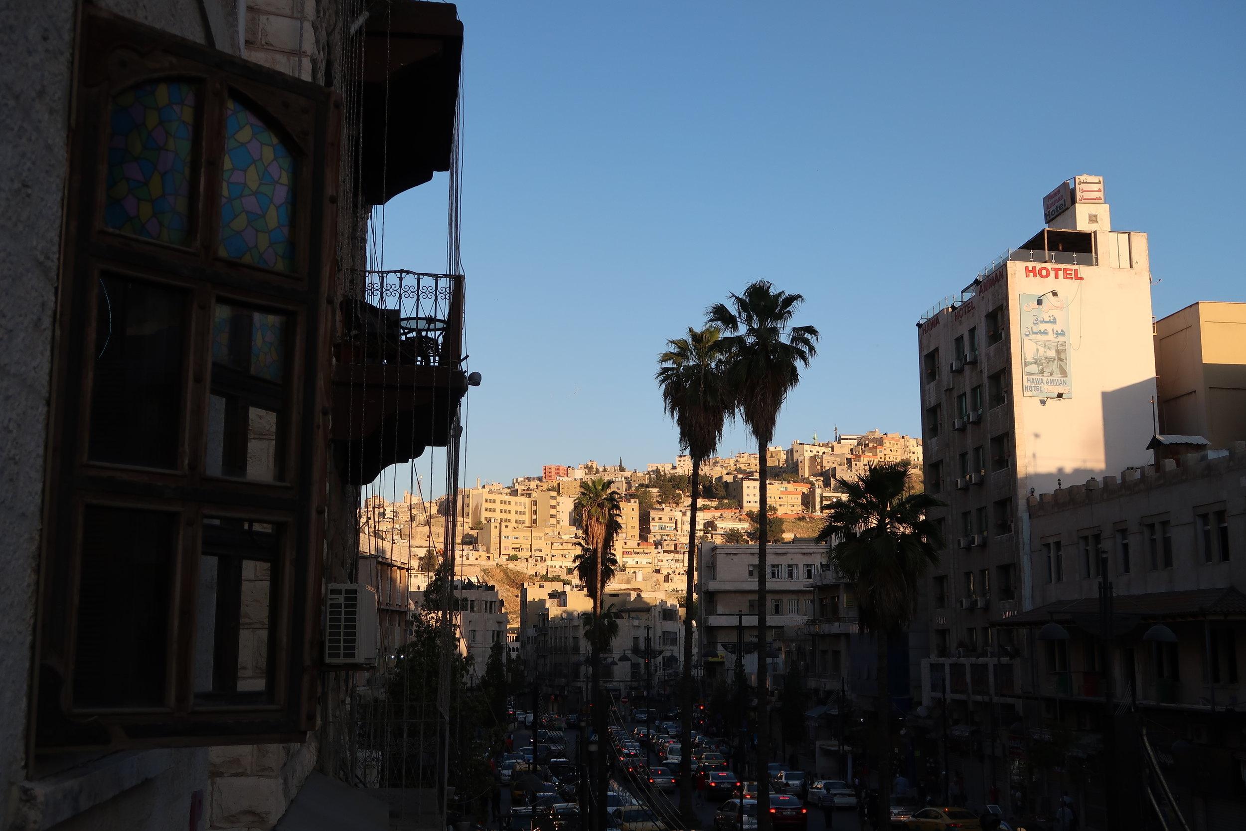从咖啡馆阳台往左手边看到大街上的车辆,以及山丘上的房屋