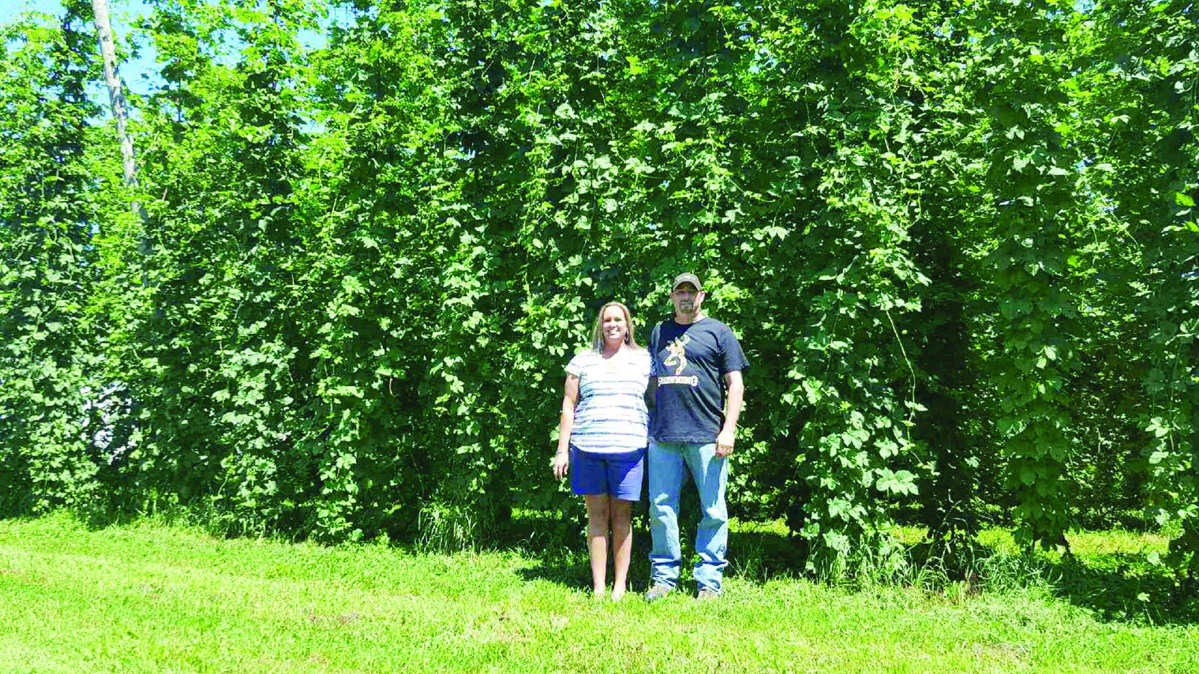 France and Yan Desjardins are pictured in front of hop plants at their Brooks-Bridge Hops farm near Grand Falls, N.B. (Submitted photo)