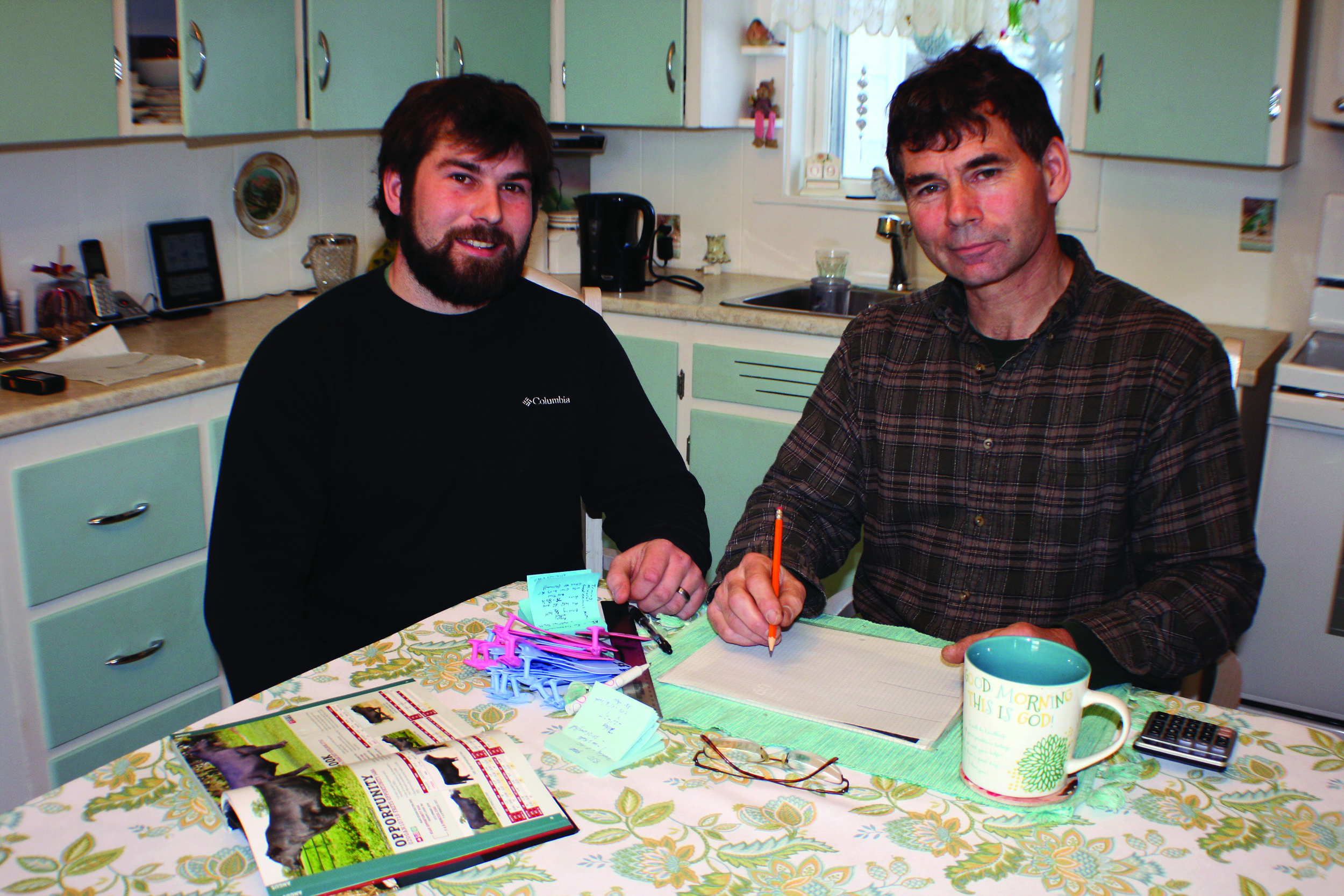 Nathan Murray, left, and his father Robert own and operate Tantramar Acres Farm. Their work includes plenty of planning sessions at the kitchen table. (Joan LeBlanc photo)