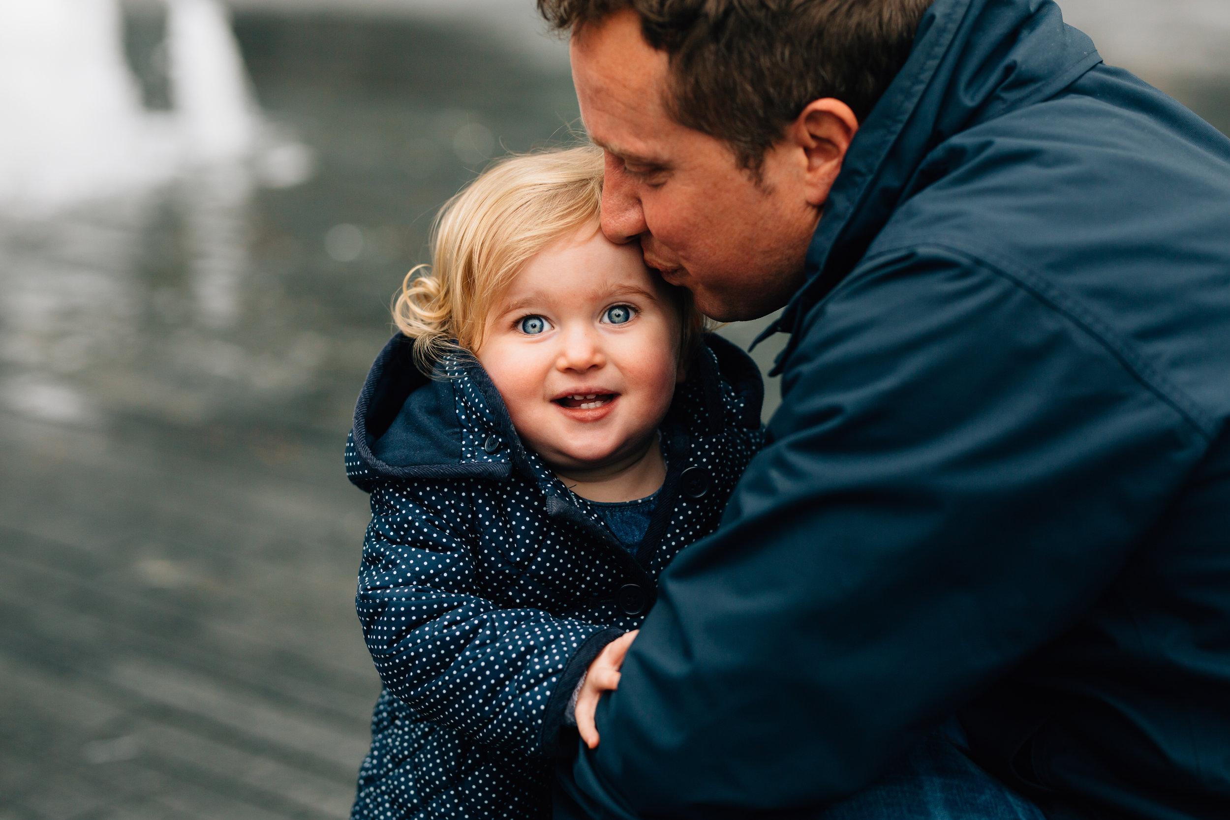 Toddler cuddles dad near Tower Bridge London
