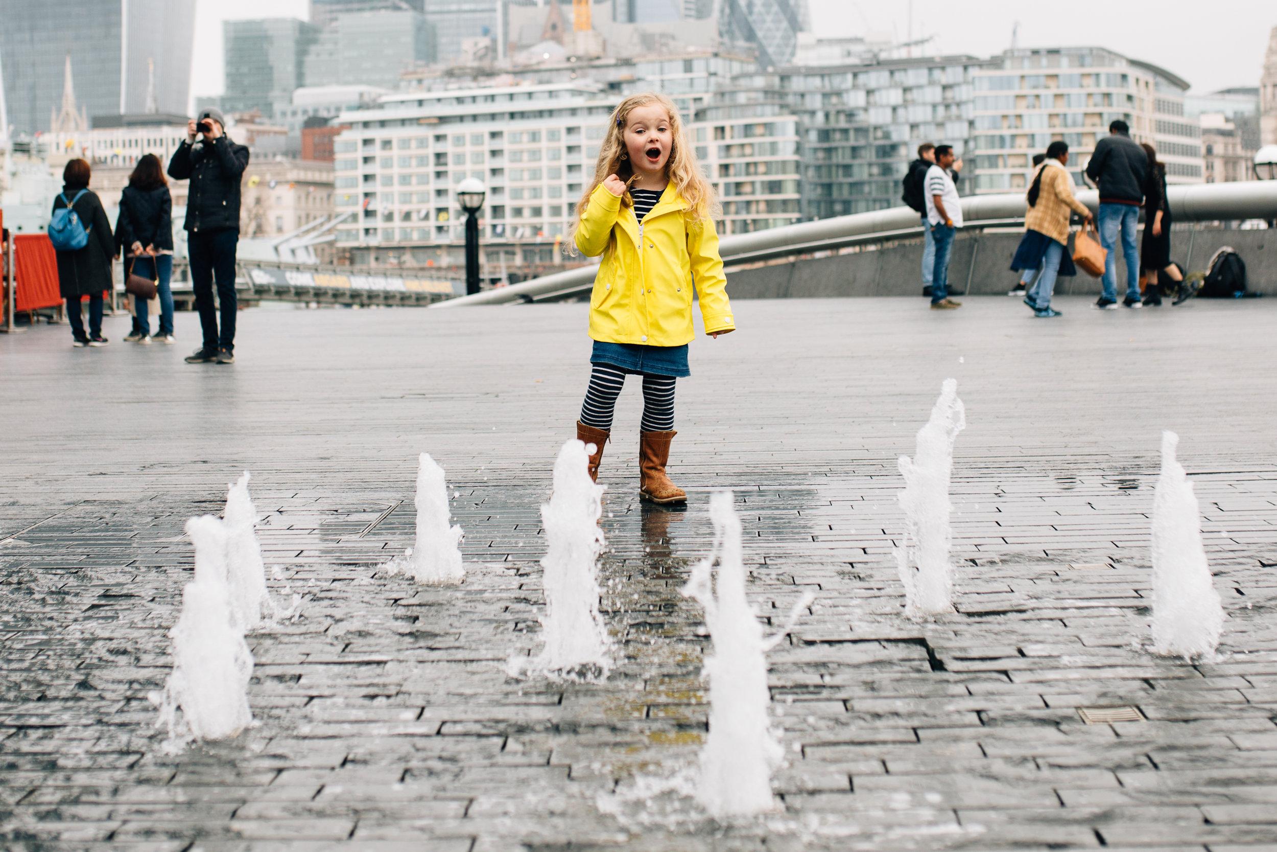 Girl runs through water fountains on family photoshoot at Tower Bridge London