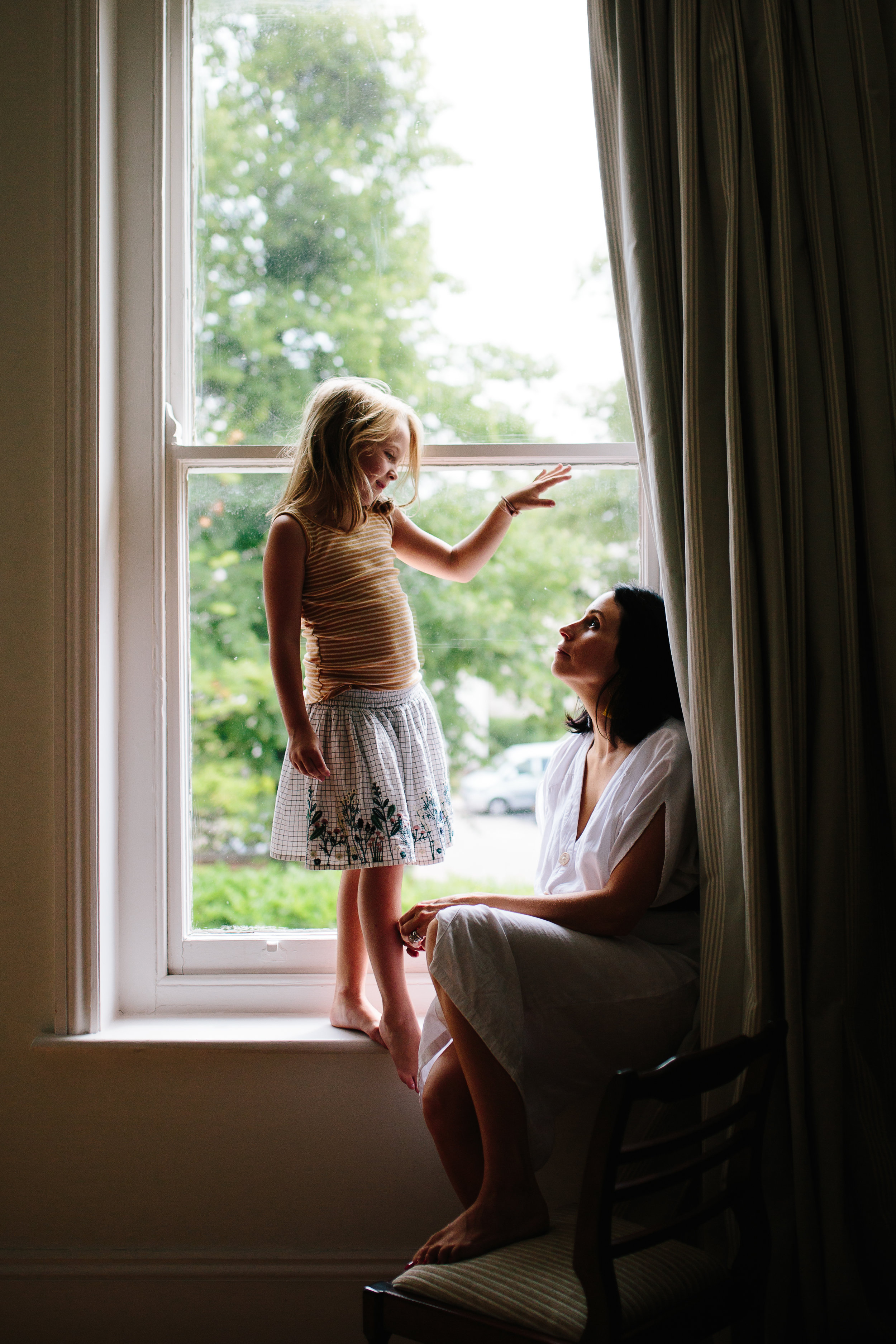 Mum and daughter in window light