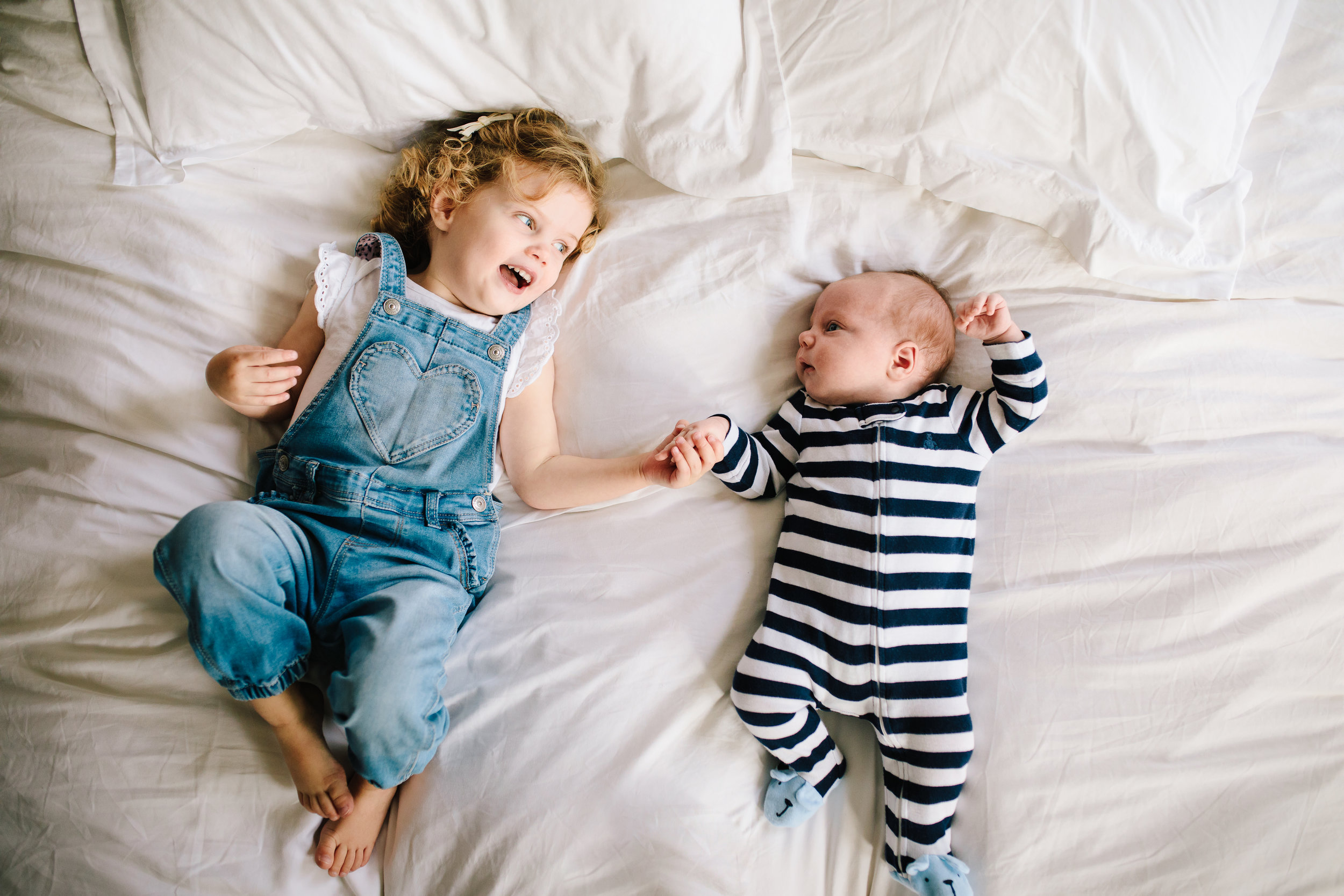 Toddler sister with newborn baby brother