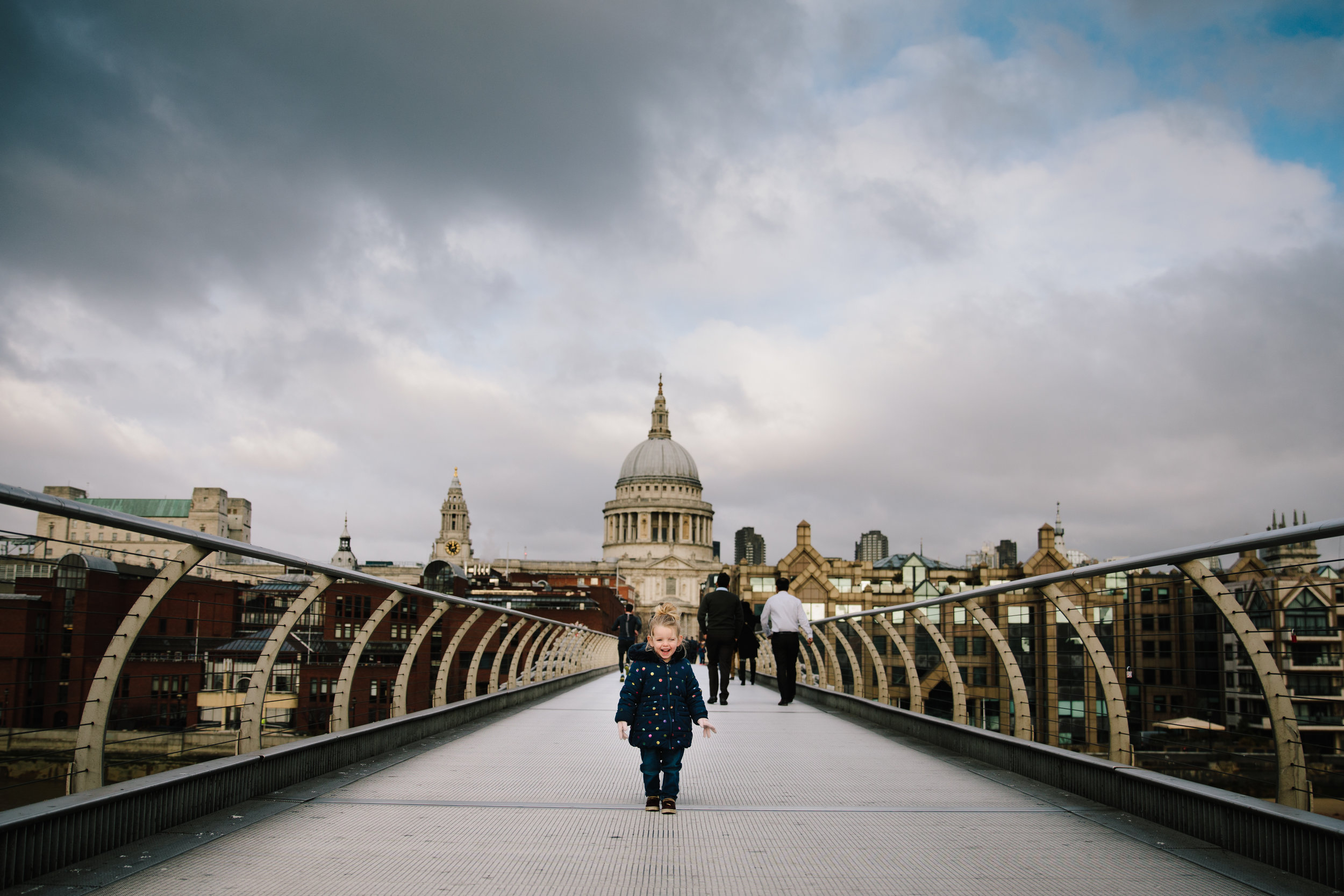 Toddler standing infront of St Paul's Cathedral on the Millennium Bridge