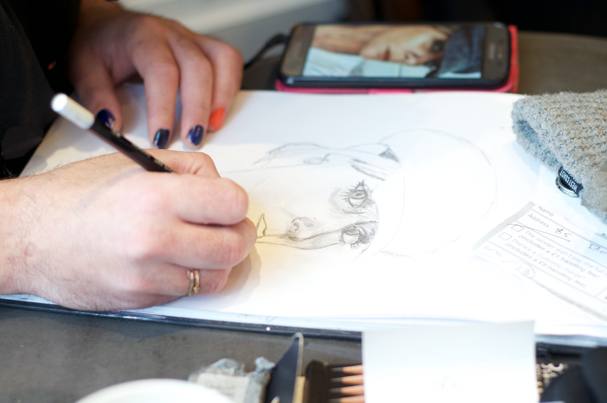 A customer at Paper and Cup takes time out to draw a portrait based on a photo on his phone.