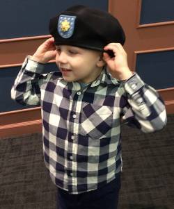A common sight with military kids - trying on parts of the uniform!