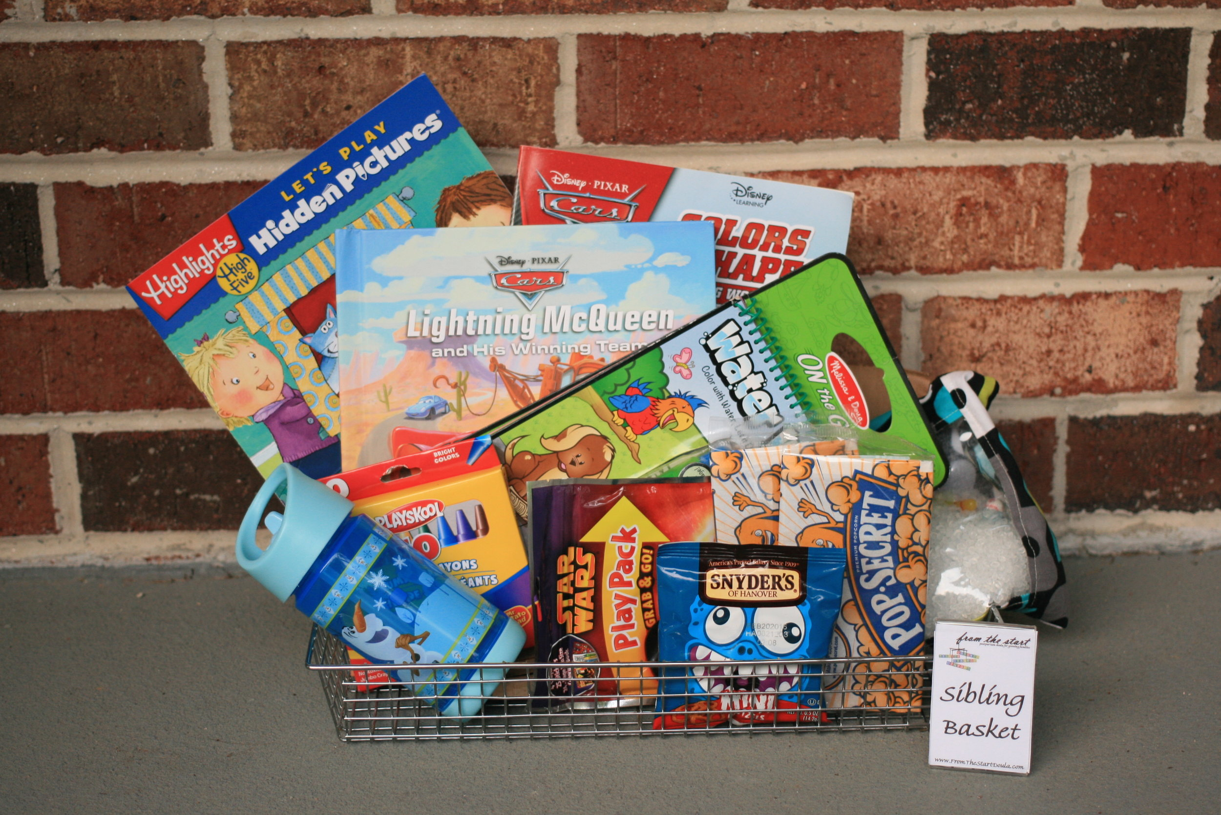 One example of a sibling basket - single serve snacks, recordable book, water bottle, I Spy bag, hidden pictures magazines and a paint-with-water book.