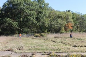 Volunteers work to mow untamed land. This was once the site of subsidized housing, and is soon to be part of a youth farm to help educate the community about horticulture and food production. (Katy Mumaw photo)