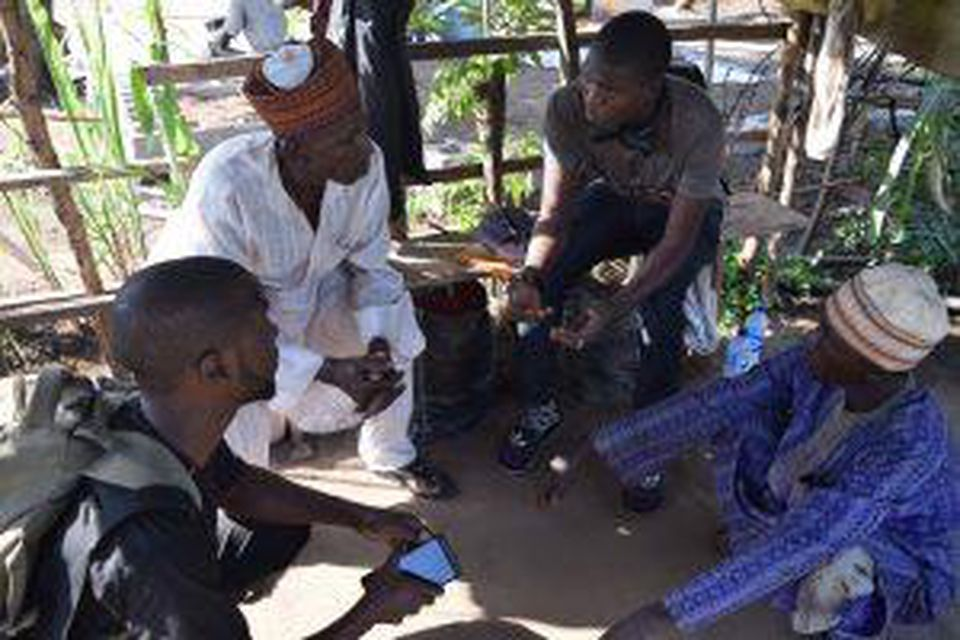 Two Hello Tractor booking agents speak with farmers about available services.(PHOTO: HELLO TRACTOR)