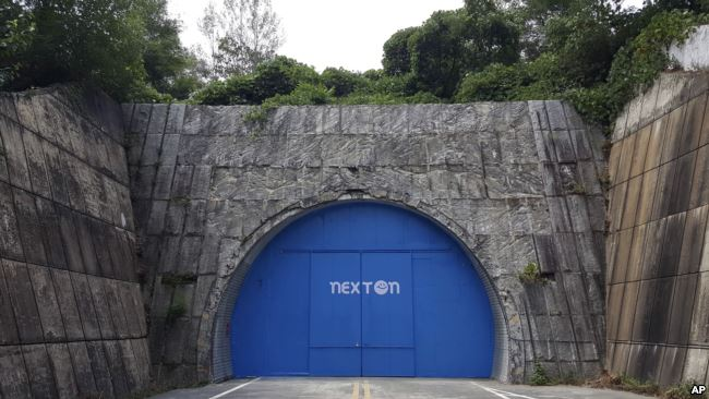 In this Aug. 9, 2018 photo, a set of bright blue doors covers the entrance of the tunnel that holds the farm NextOn in Okcheon, South Korea.(AP Photo/Han Myung Oh)