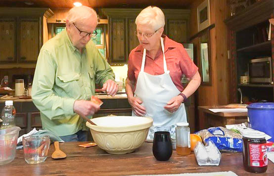 Seen here is Jean Sasso in Gannaiden's kitchen preparing the Roly Poly recipe while her assistant Marcel Braitstein opens a yeast package
