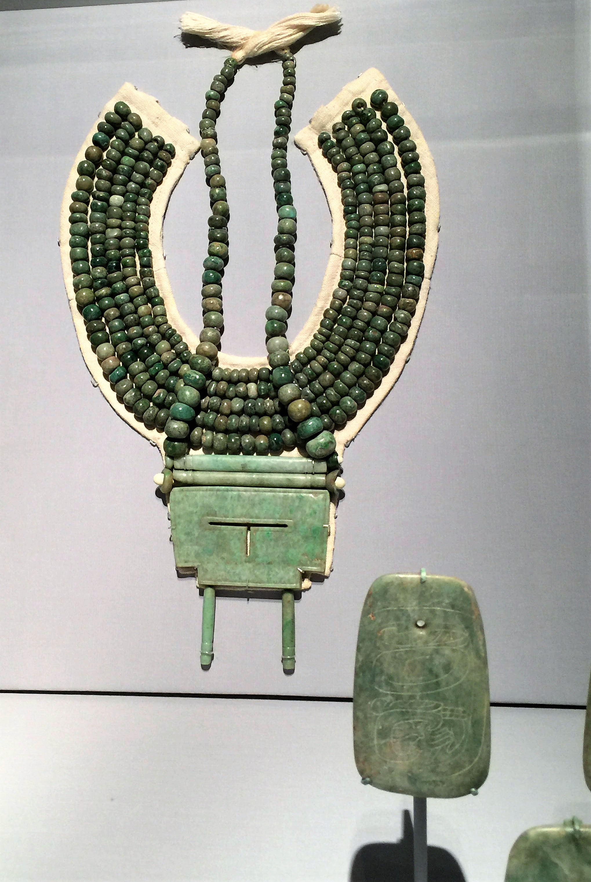 Highly prized by pre-Columbians civilization was jade. - This massive jade pectoral and necklace were part of an assemblage discovered in a tomb at Calakmul. The large plaque is in the shape of the hieroglyphic logogram for ik', meaning