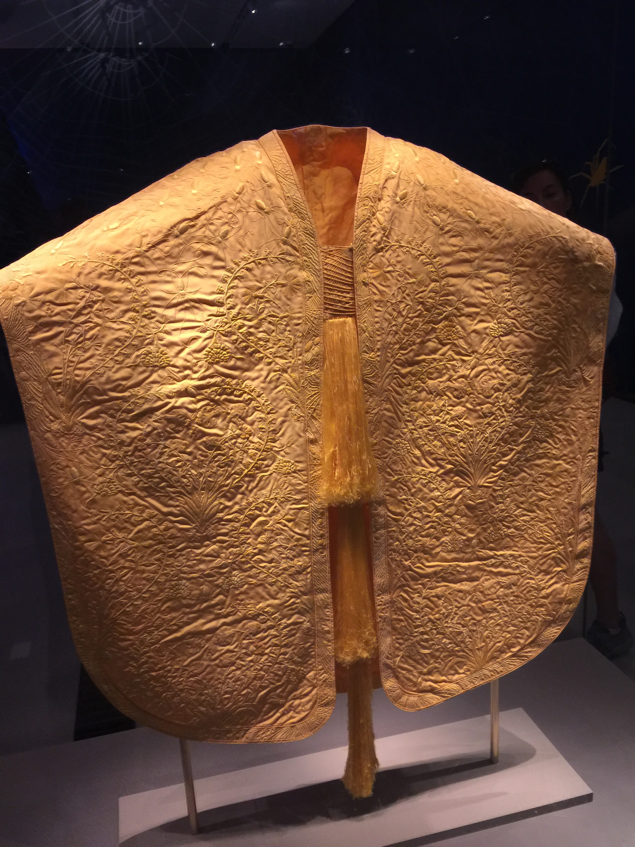 Golden Spider Silk Cape - Resplendent in a glass case in the middle of a dark room at the ROM, is a golden cape woven from the silk of 1.2 million gold-orb weaver spiders.