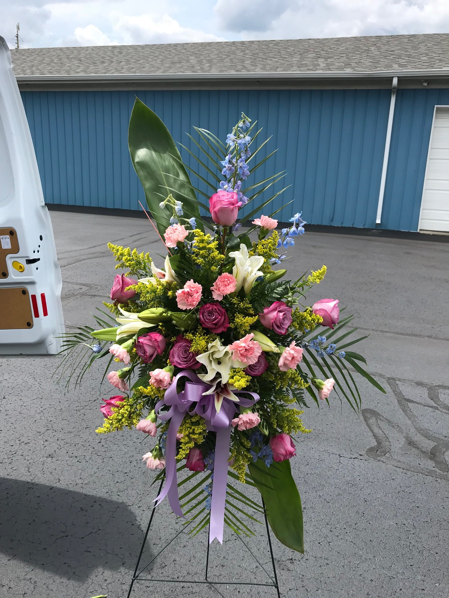 Easel Spray - $ 295.00Lavender Rose, Pink Carnation, White Oriental Lily, Stargazer Lily, Blue Delphinium, Solidago, Large Tea Leaf.