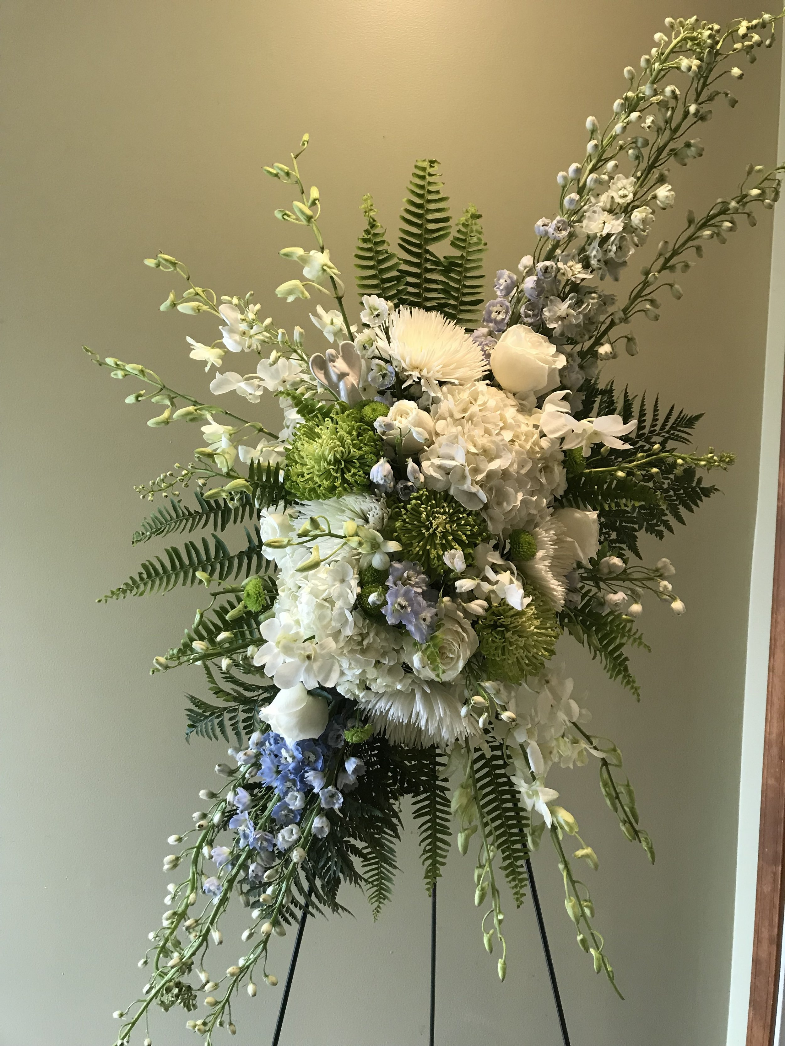 Easel Spray - $ 300.00White Orchid, Blue Delphinium, White Rose, White and Green Spider Mum,Green Button Mum, White Hydrangea.