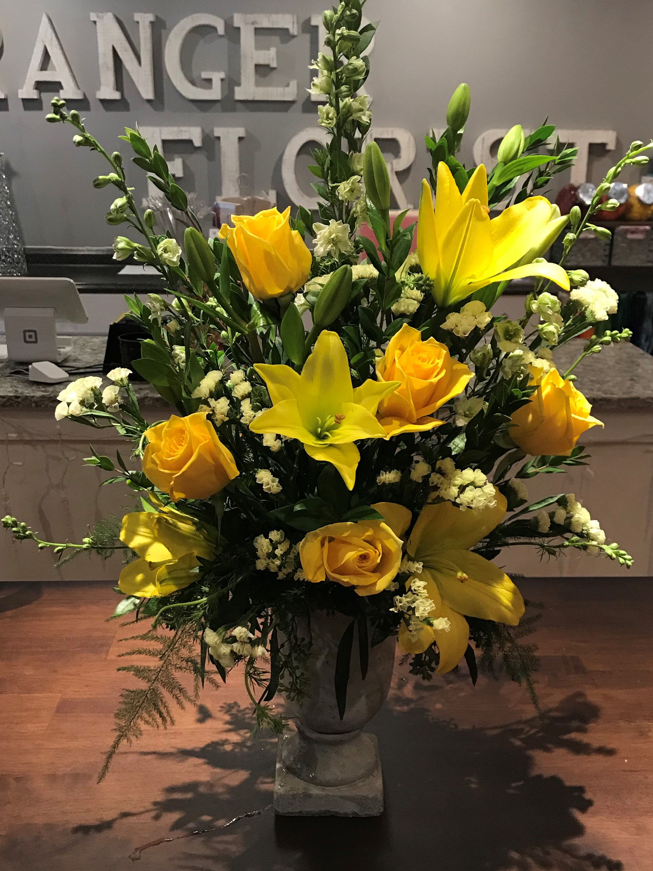 Urn Spray - $ 125.00Yellow Rose, Yellow Asiatic Lily, White Status, Blue Delphinium, Myrtle.