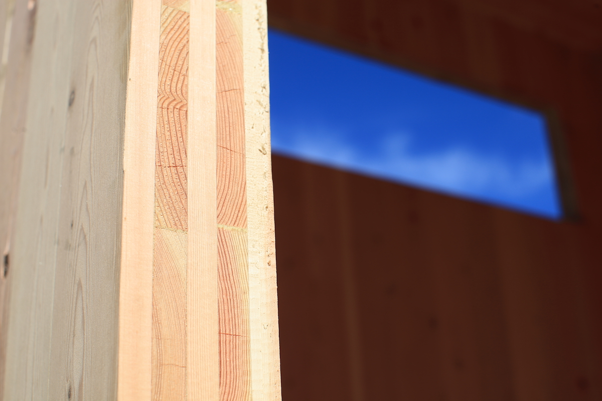 A cross-laminated timber wall, five layers of 1x6 Douglas Fir, glued into sheets then pressed into a panel with each layer's grain running perpendicular.