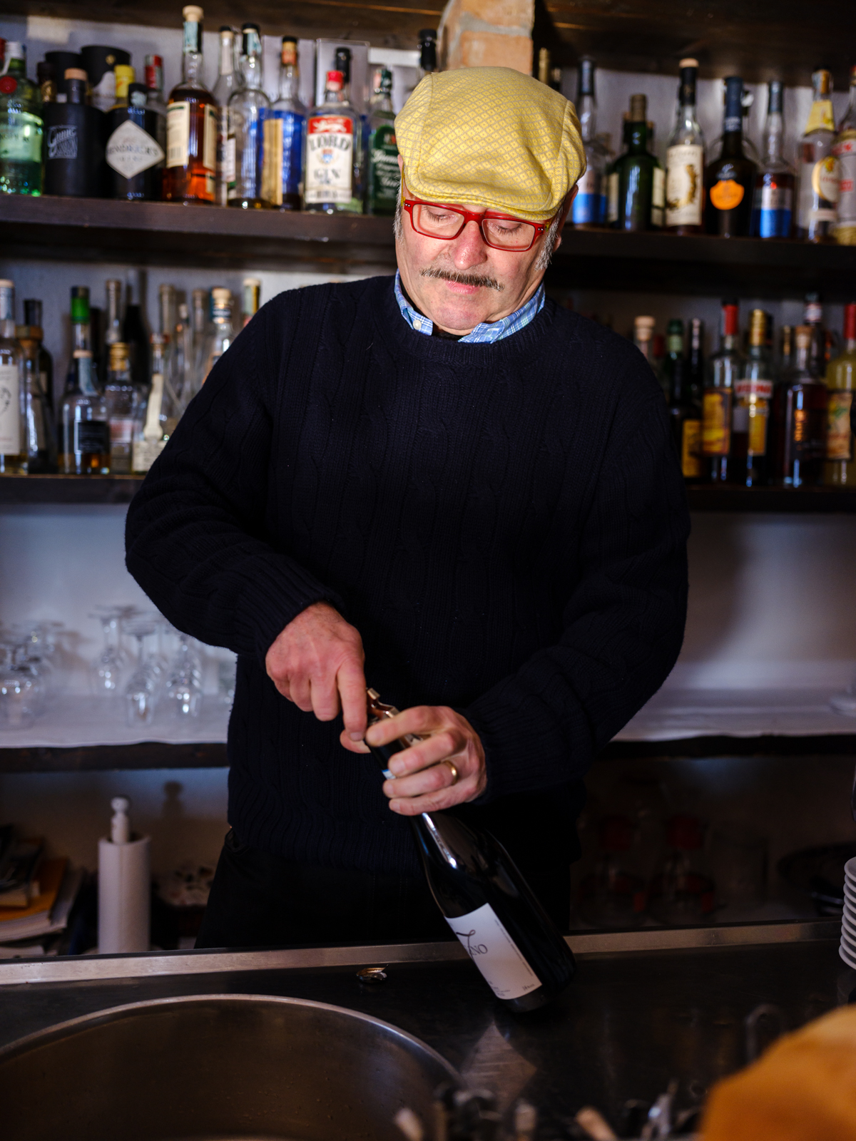 Gino, owner of ristorante Belbo Da Bardon, opening a bottle wine in his restaurant (f/2.8, 1/160s, ISO 1600)