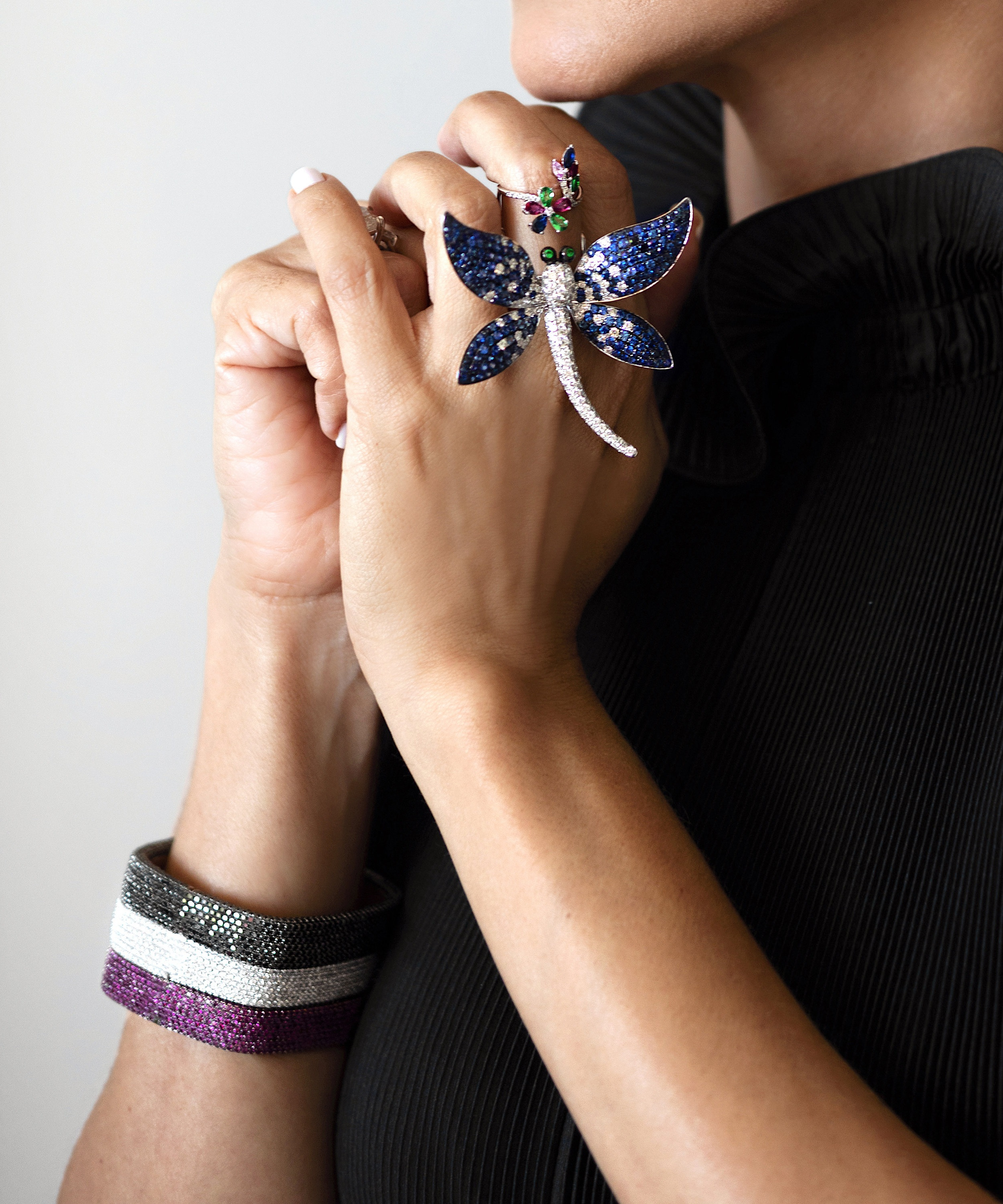 Patricia wears her signature square bangles in black diamonds, white diamonds and rubies, all in 18k gold. Her sapphire dragonfly ring is also hand made in 18k white gold.