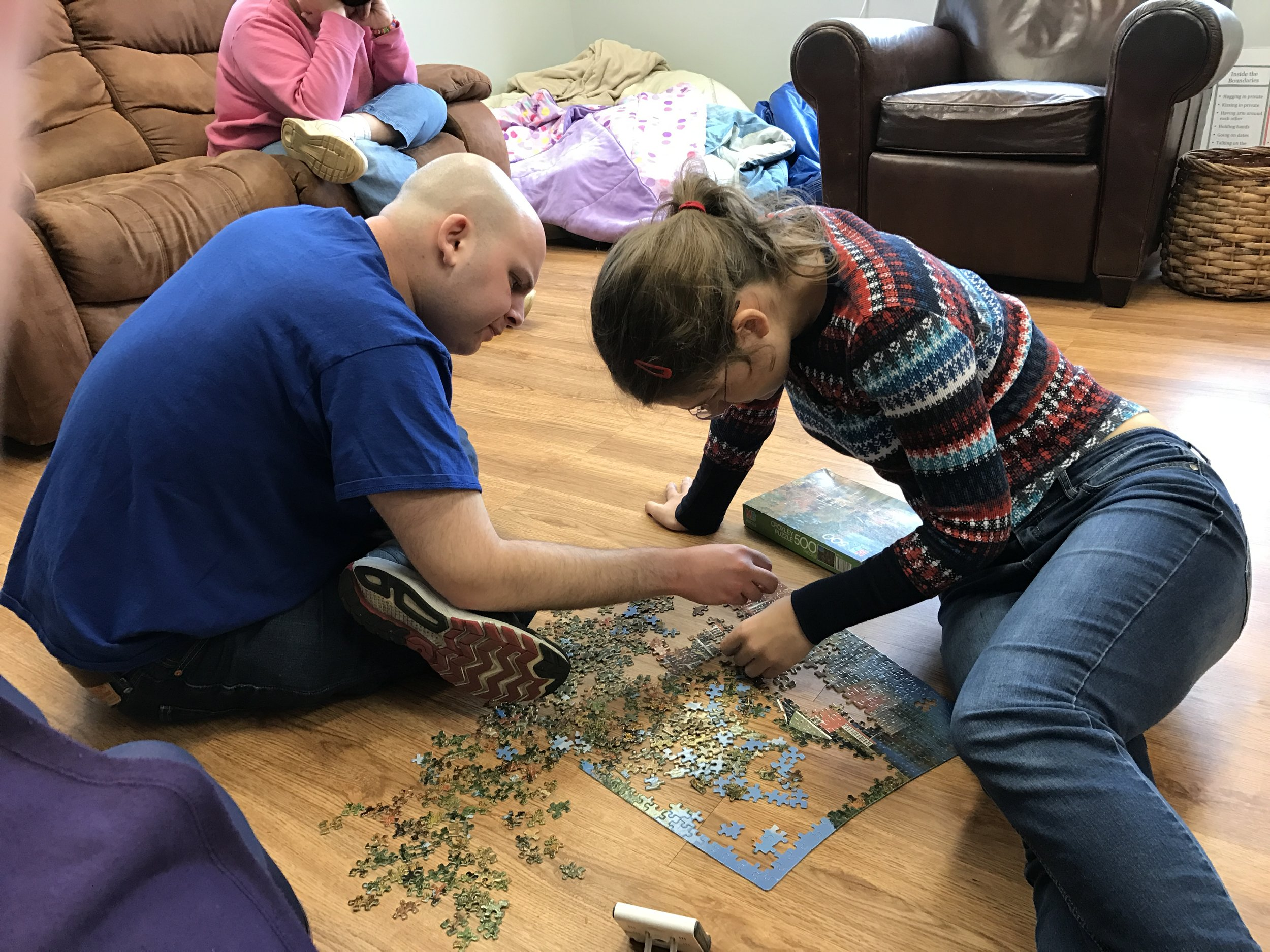 Two friends at Our Place working on a puzzle together