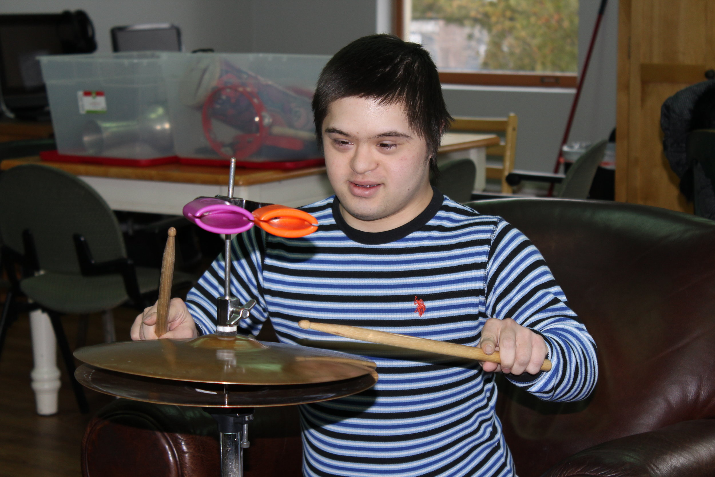 A male Our Place participant is using drumsticks on a cymbal