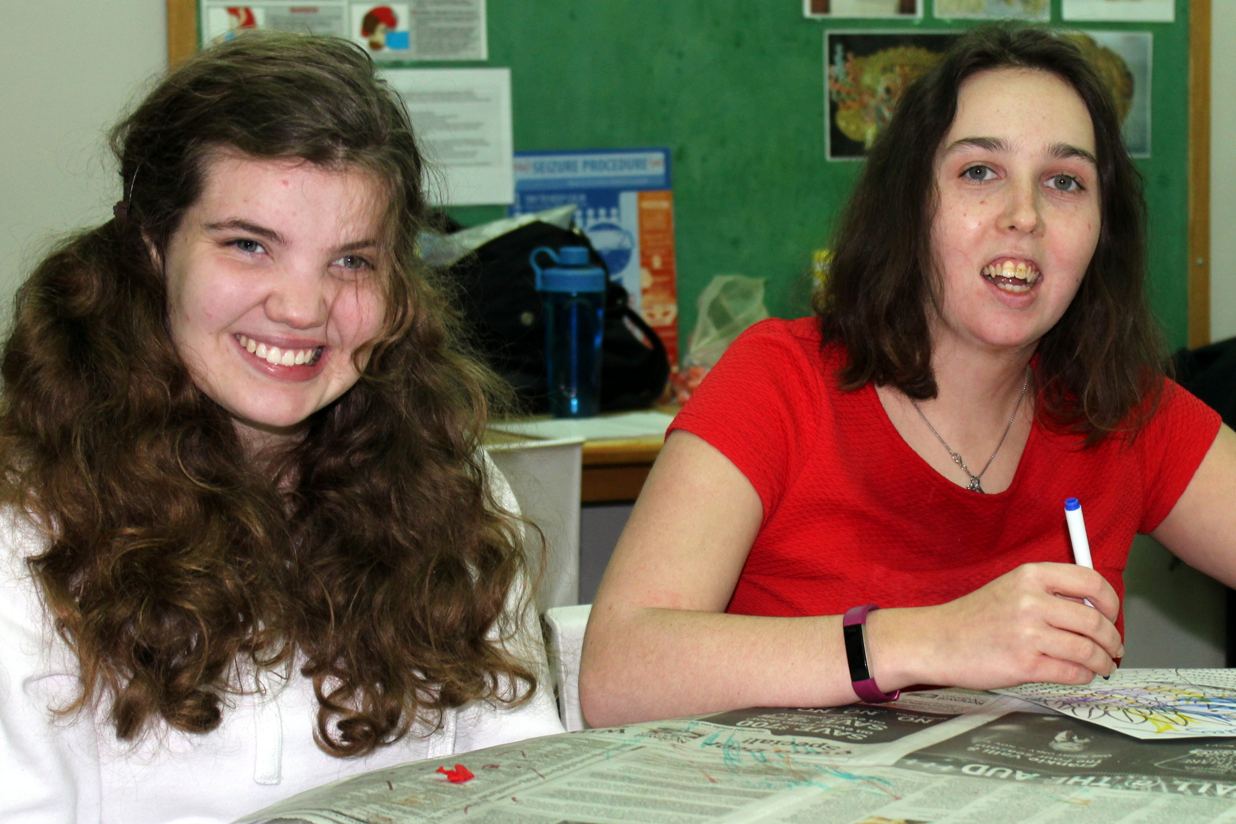 Two female participants smiling, drawing in an art program