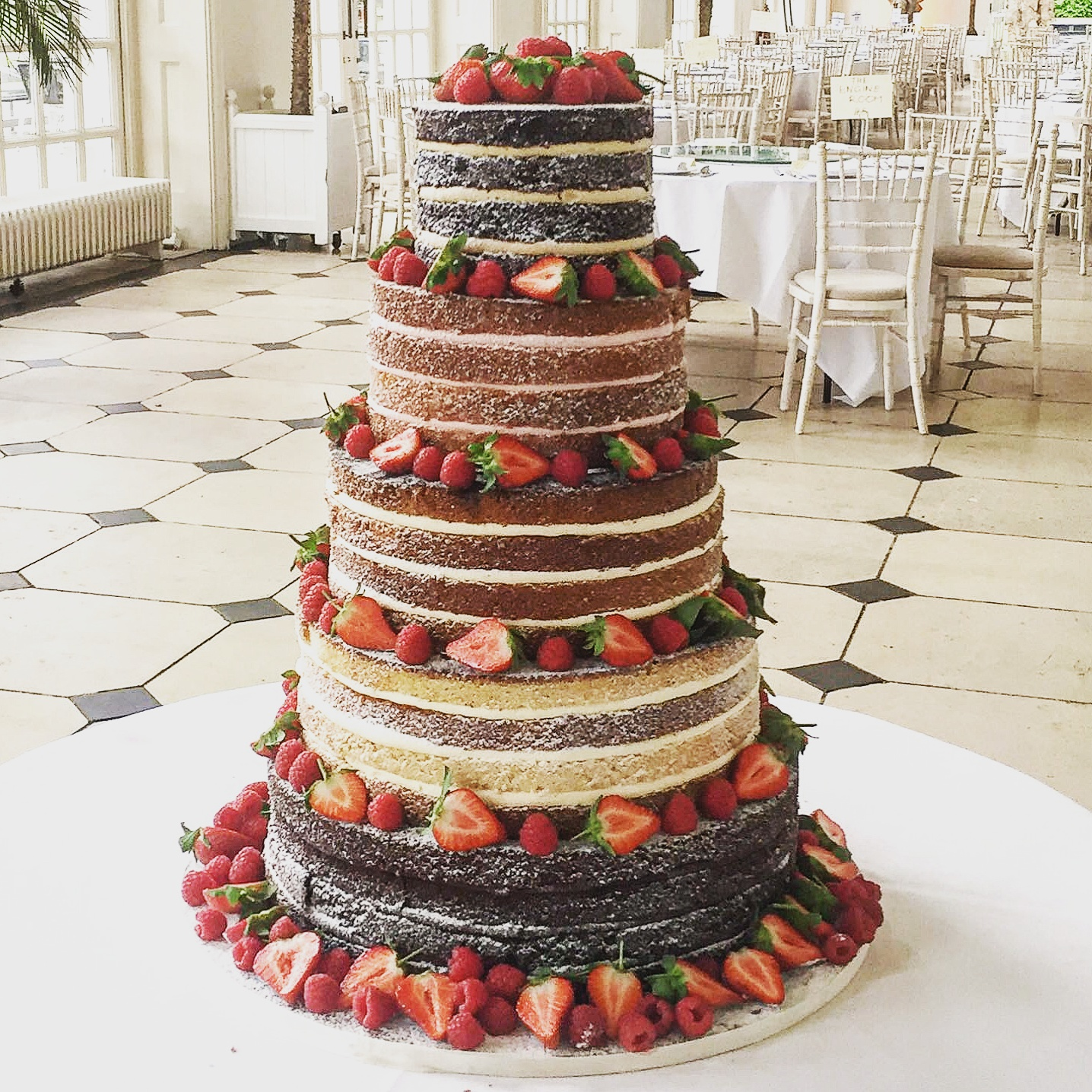 Tiered naked cake with different flavours and berries