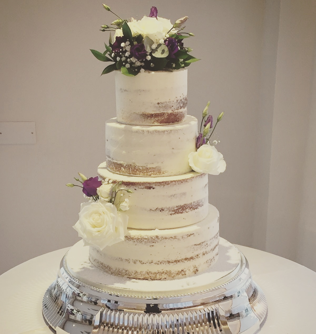 Skimmed naked cake, with vanilla buttercream and white flowers